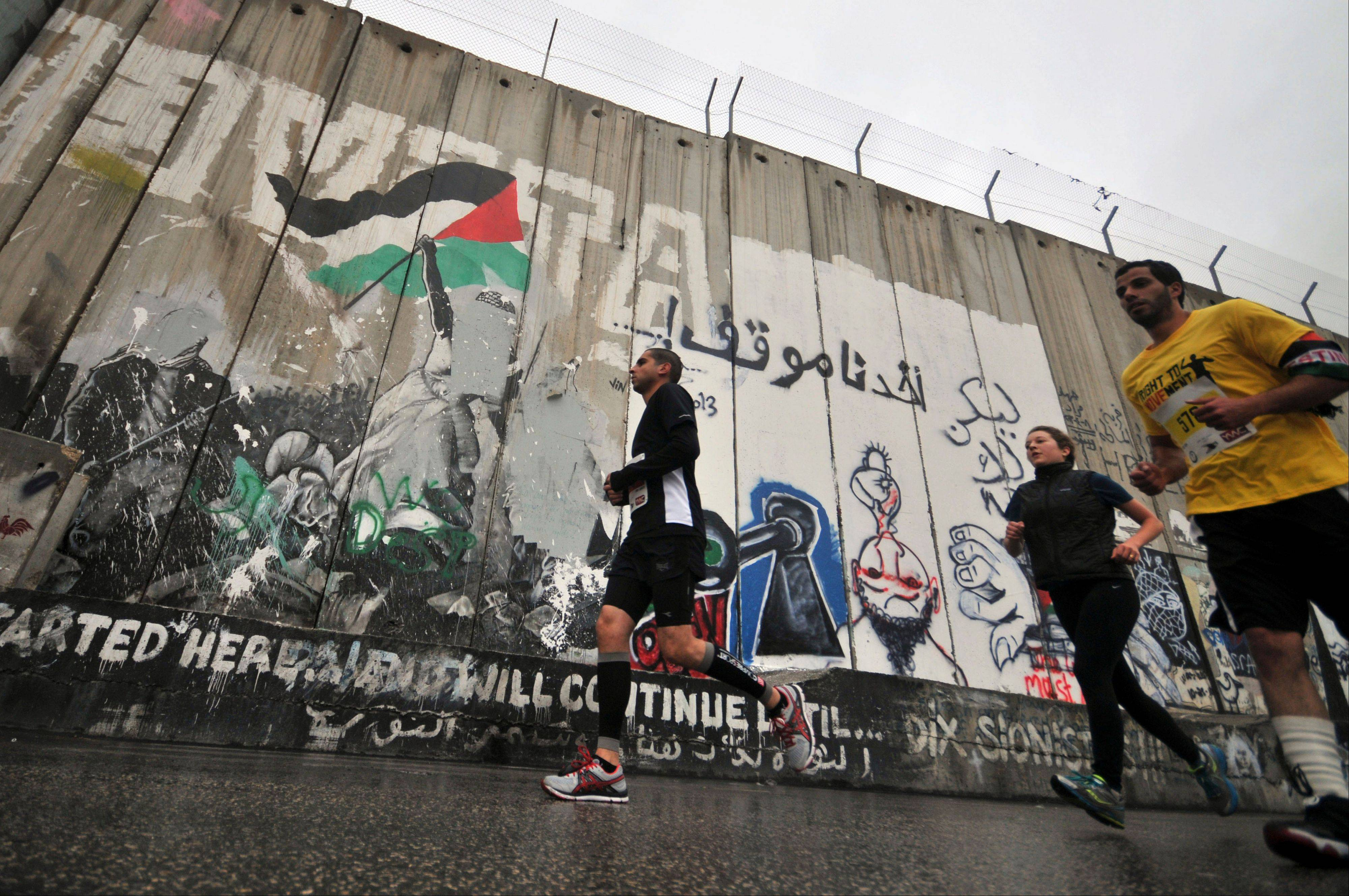 People run past the separation wall Sunday during the West Bank�s first marathon in Bethlehem. About 1,000 people participated in the race, which included shorter 10-kilometer and 20-kilometer options.