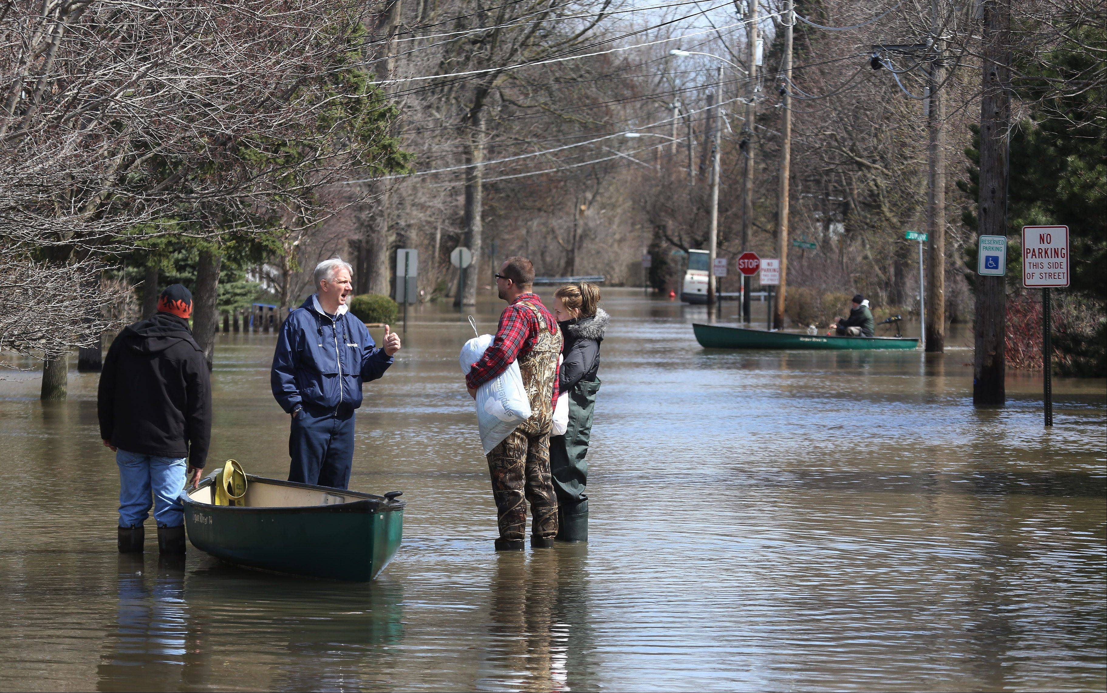The mode of transportation around Des Plaines neighborhoods on Sunday is by canoe, as Vic Kamka, center, talks to neighbors after flooding along the Des Plaines River.