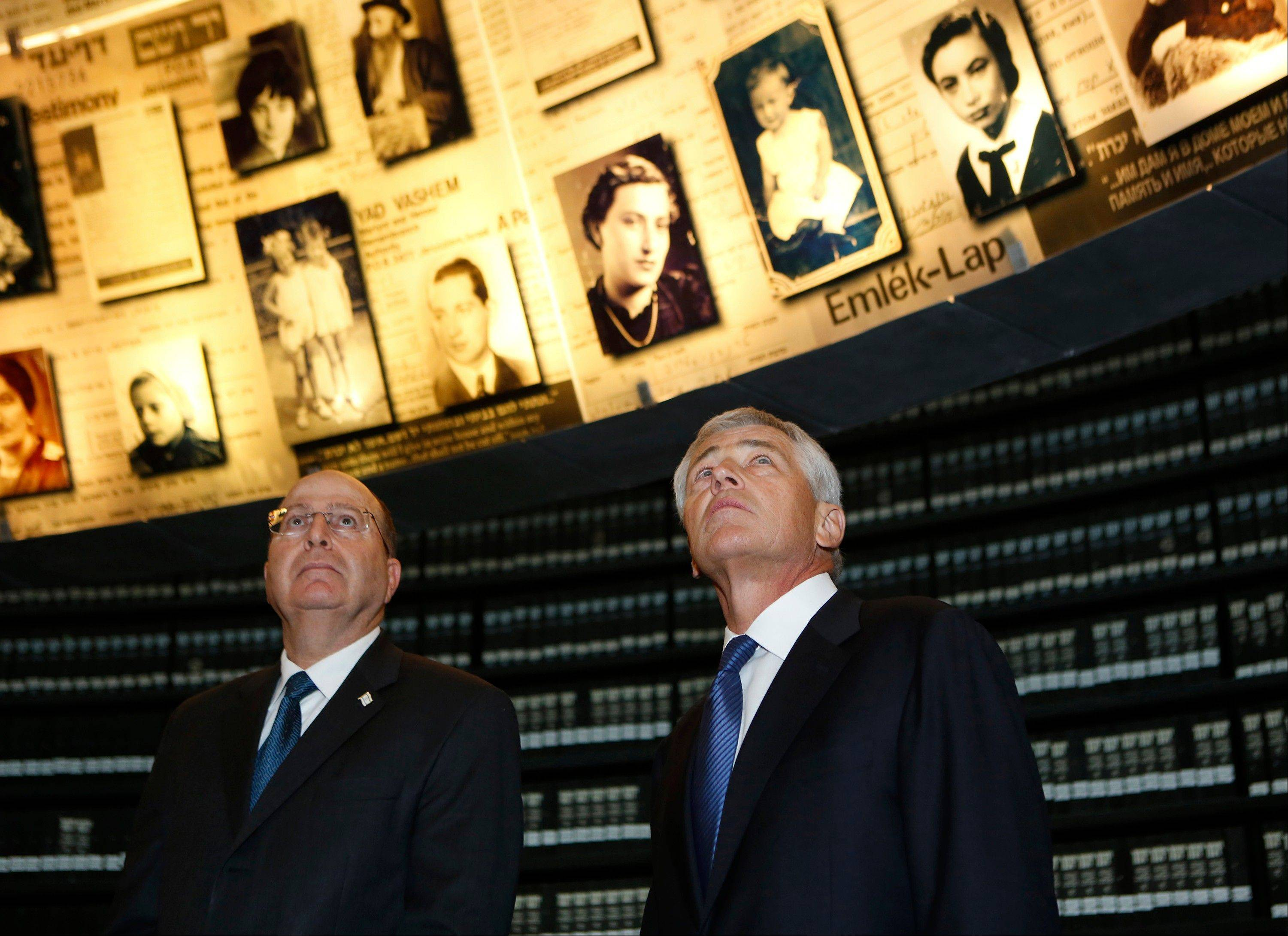U.S. Defense Secretary Chuck Hagel, right, stands next to Israel�s Defense Minister Moshe Yaalon as he looks at pictures of Jews killed in the Holocaust during a Sunday visit to the Hall of Names at Yad Vashem�s Holocaust History Museum in Jerusalem.