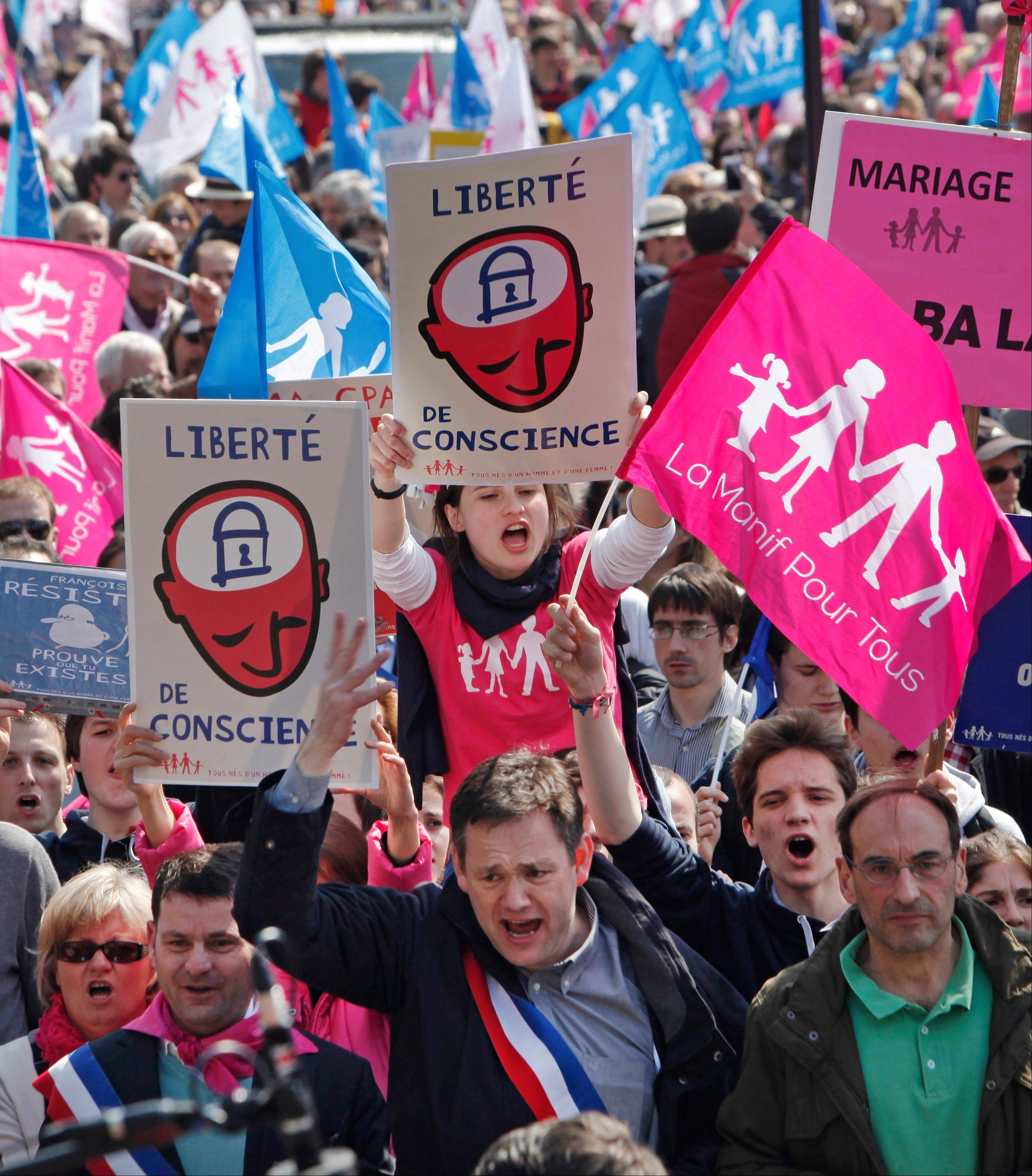 Demonstrators march during a protest Sunday of French President Francois Hollande�s social reform on gay marriage and adoption in Paris. Both houses of the French parliament have already approved the bill in a first reading. The second and final reading is expected Tuesday. Signs read: Freedom of Conscience.