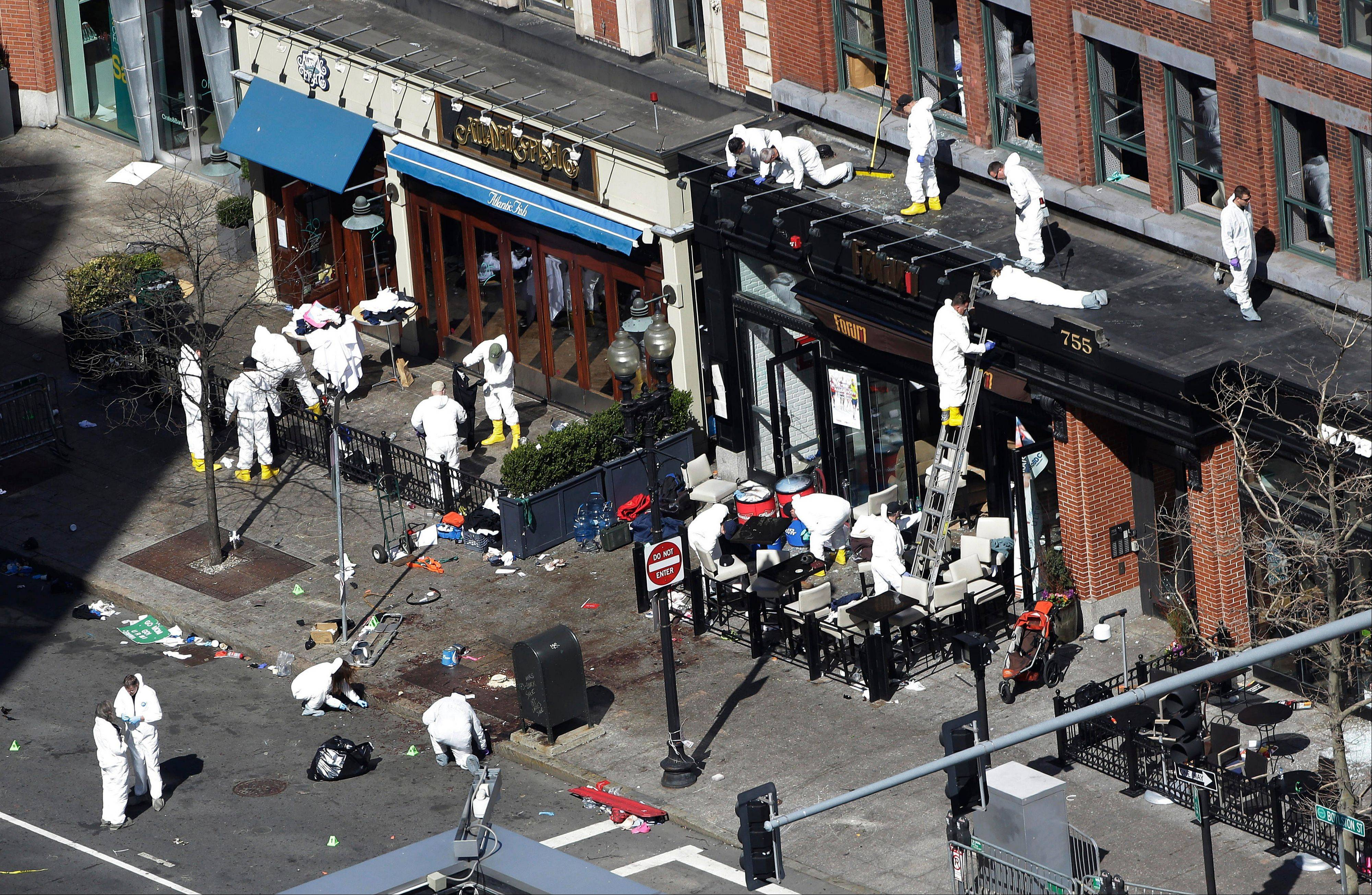 Investigators comb through the scene of one of the blast sites of the Boston Marathon on Wednesday, two days after the explosions.