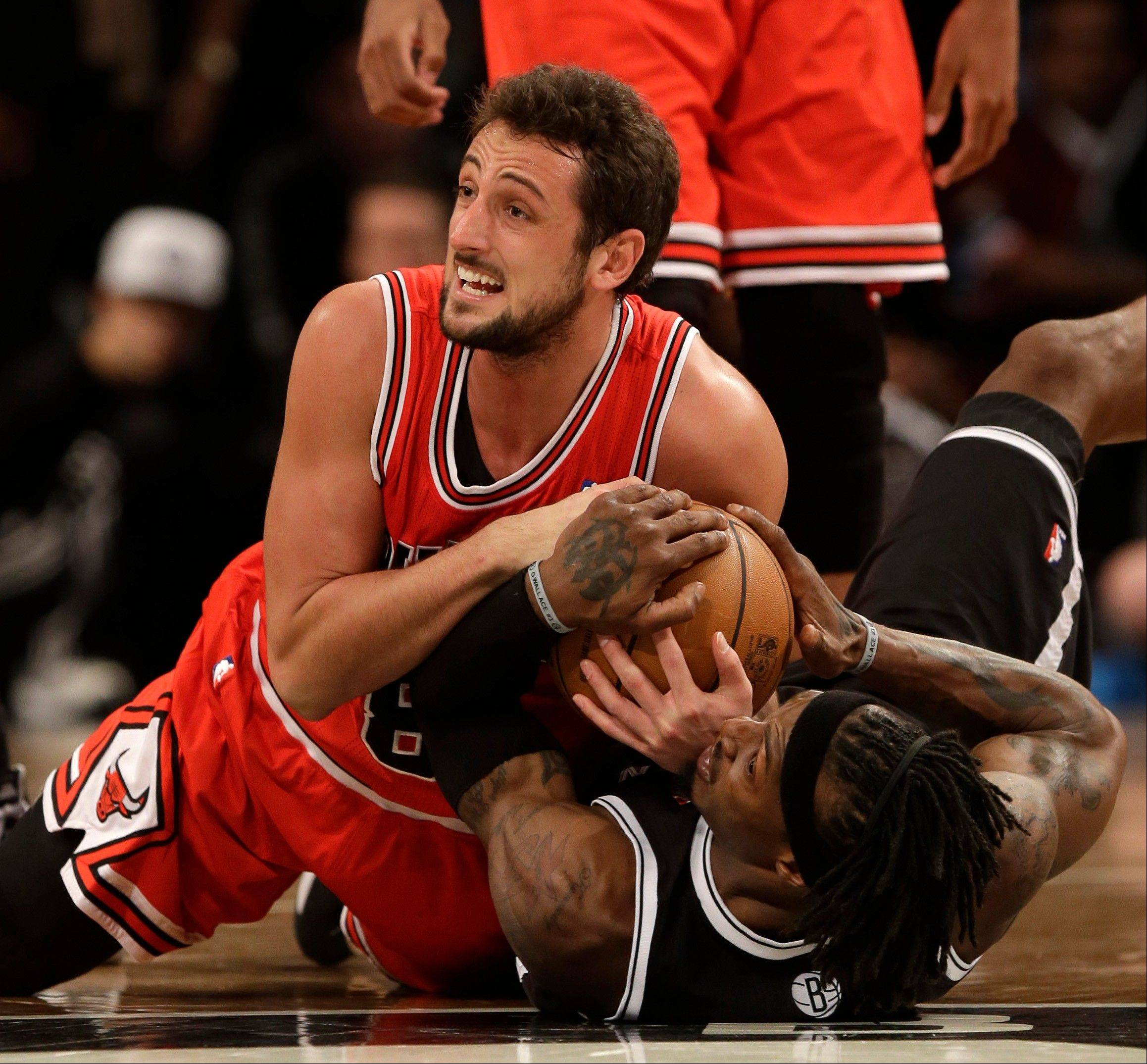Chicago�s Marco Belinelli, top, and Brooklyn�s Gerald Wallace fight for a loose ball during Saturday�s playoff game, which the Bulls lost 106-89.