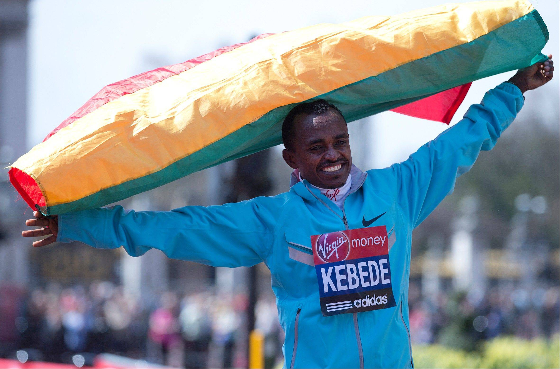 Tsegaye Kebede of Ethiopia, winner of the men�s London Marathon, holds his country�s national flag as he poses for photographs after the medal ceremony on Sunday. A defiant, festive mood prevailed Sunday as the London Marathon began despite concerns raised by the bomb attacks on the Boston Marathon six days ago.