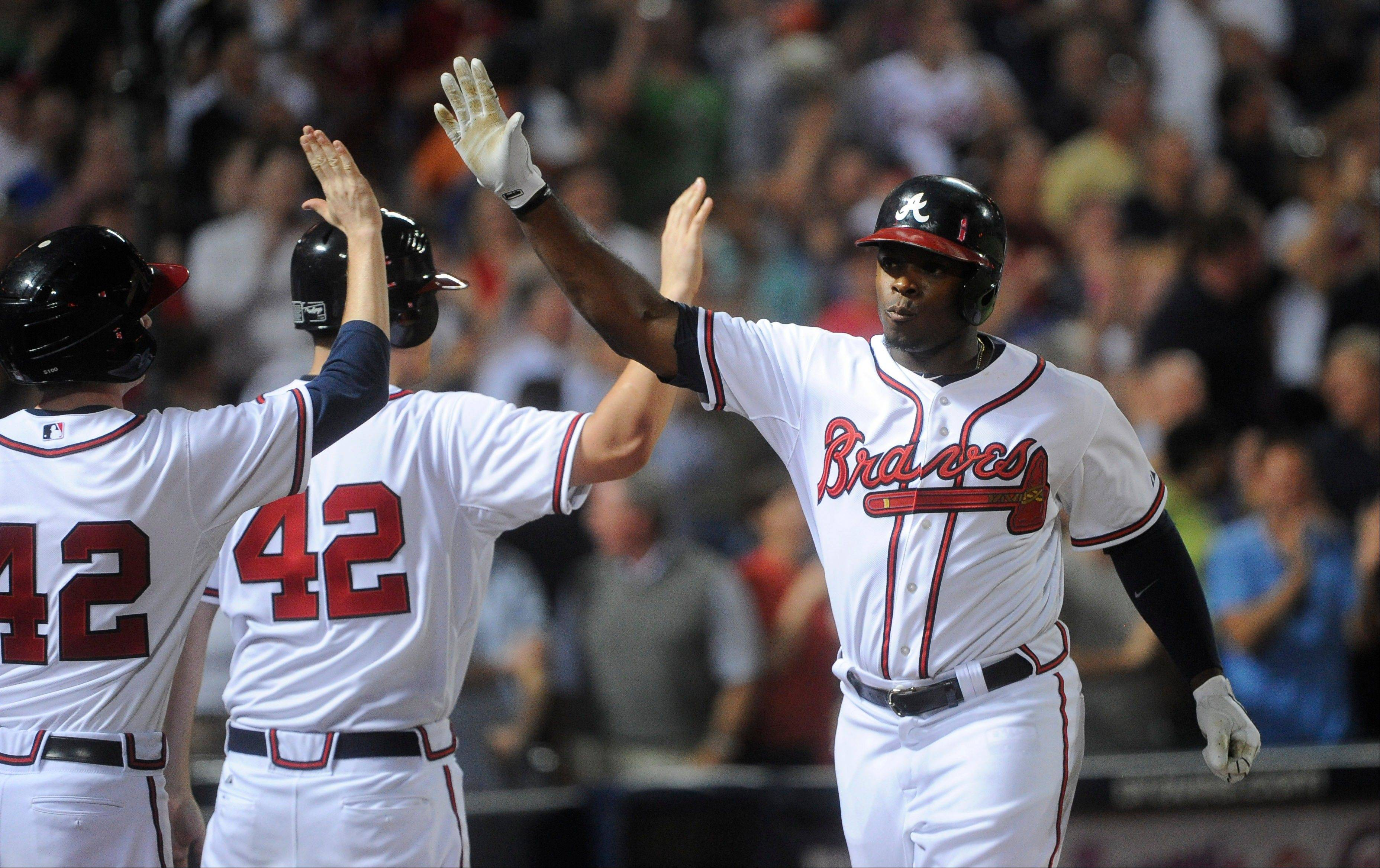 Atlanta Braves� Justin Upton, right, is congratulated as he comes back to the dugout after a home run against the Kansas City Royals during the eighth inning of a baseball game, Tuesday, April 16, 2013, in Atlanta. Atlanta won 6-3. (AP Photo/John Amis)