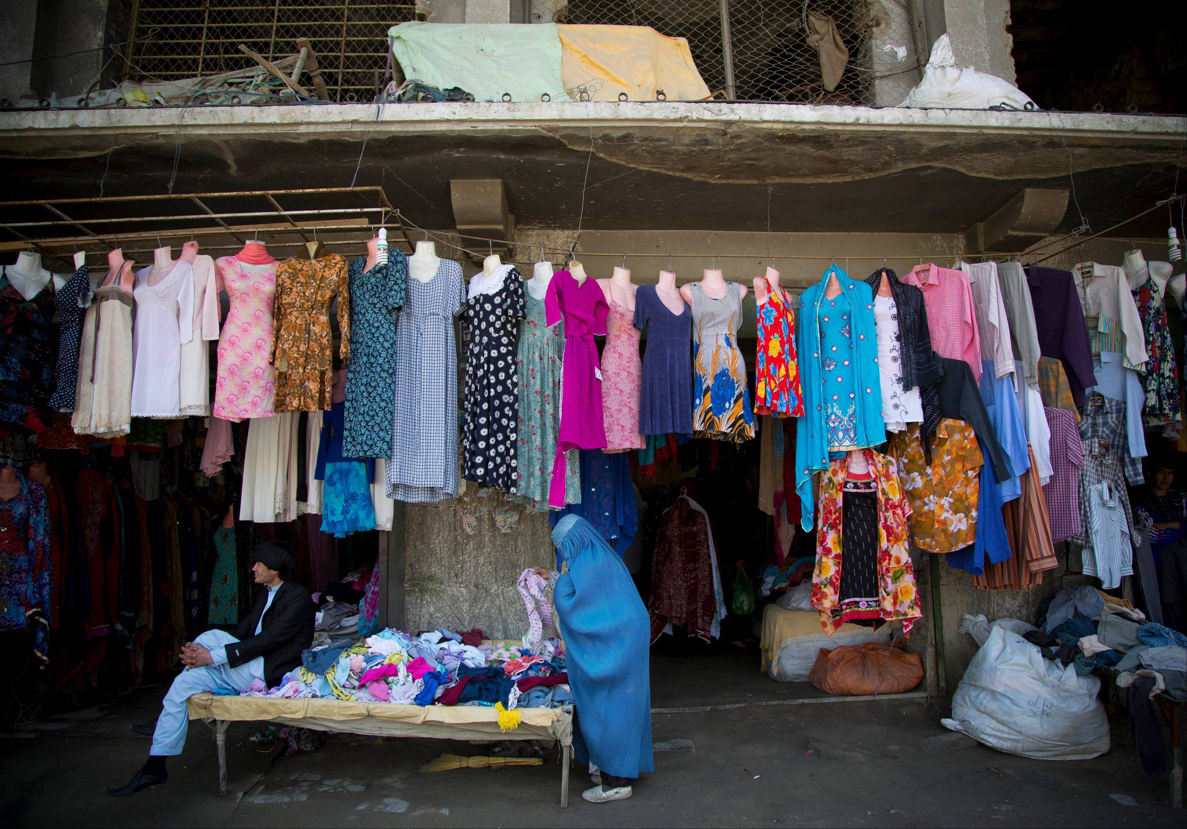 An Afghan woman shops for clothing in the old town of Kabul, Afghanistan. Despite advances in womenís rights, Afghanistan remains a deeply conservative country and most women continue to wear the Burqa. But tradesmen say times are changing in Kabul at least, with demand for burqas declining as young women going to school and taking office jobs refuse to wear the cumbersome garments.