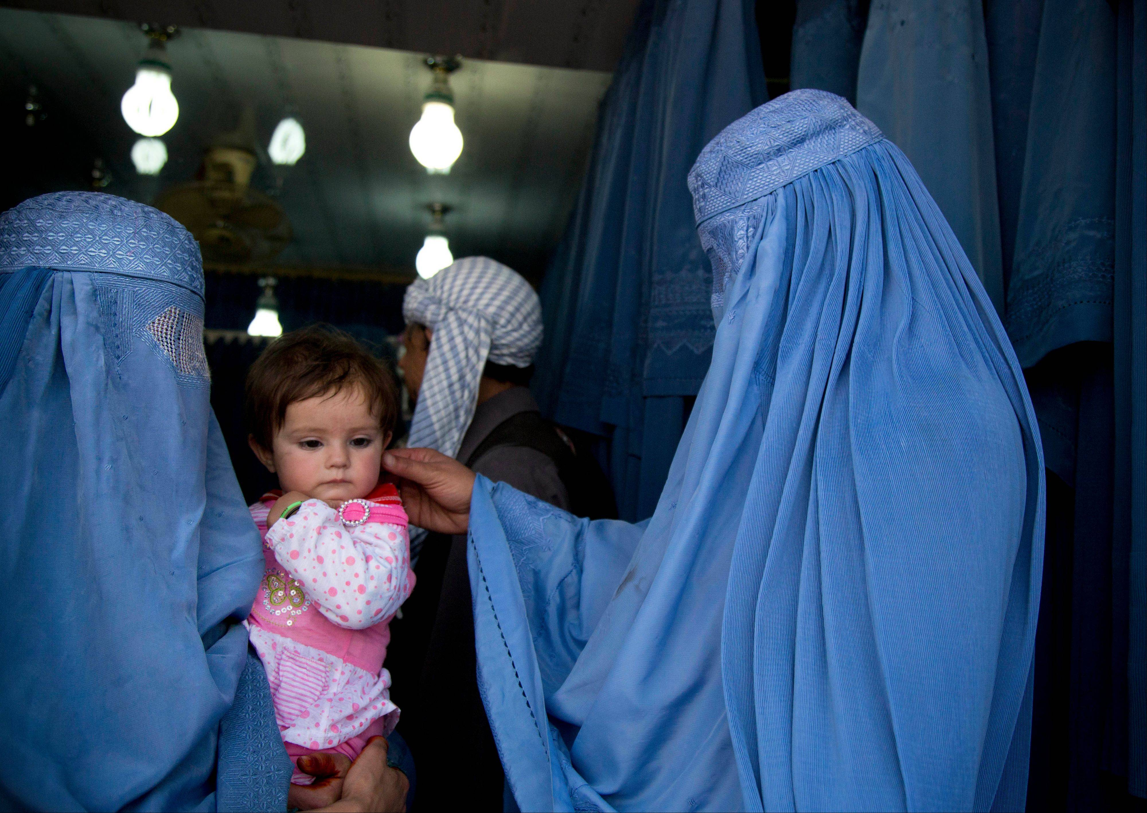 An Afghan woman comforts the child of her friend as both wait to get in line to try on a new burqa in a shop in the old town of Kabul, Afghanistan. Despite advances in womenís rights, Afghanistan remains a deeply conservative country and most women continue to wear the Burqa. But tradesmen say times are changing in Kabul at least, with demand for burqas declining as young women going to school and taking office jobs refuse to wear the cumbersome garments.
