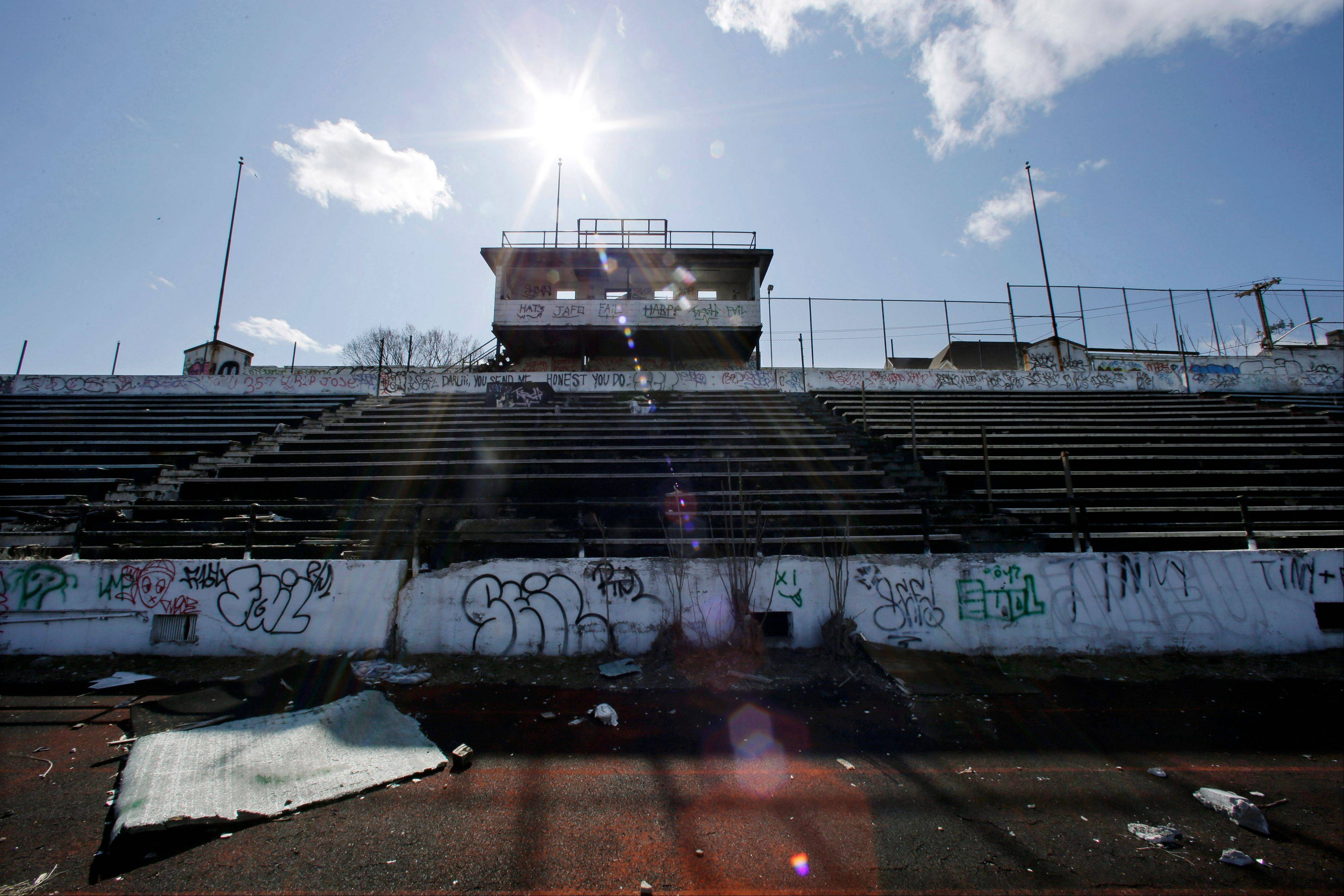 A graffiti-covered press box and deteriorated artificial turf in Hinchliffe Stadium in Paterson, N.J.