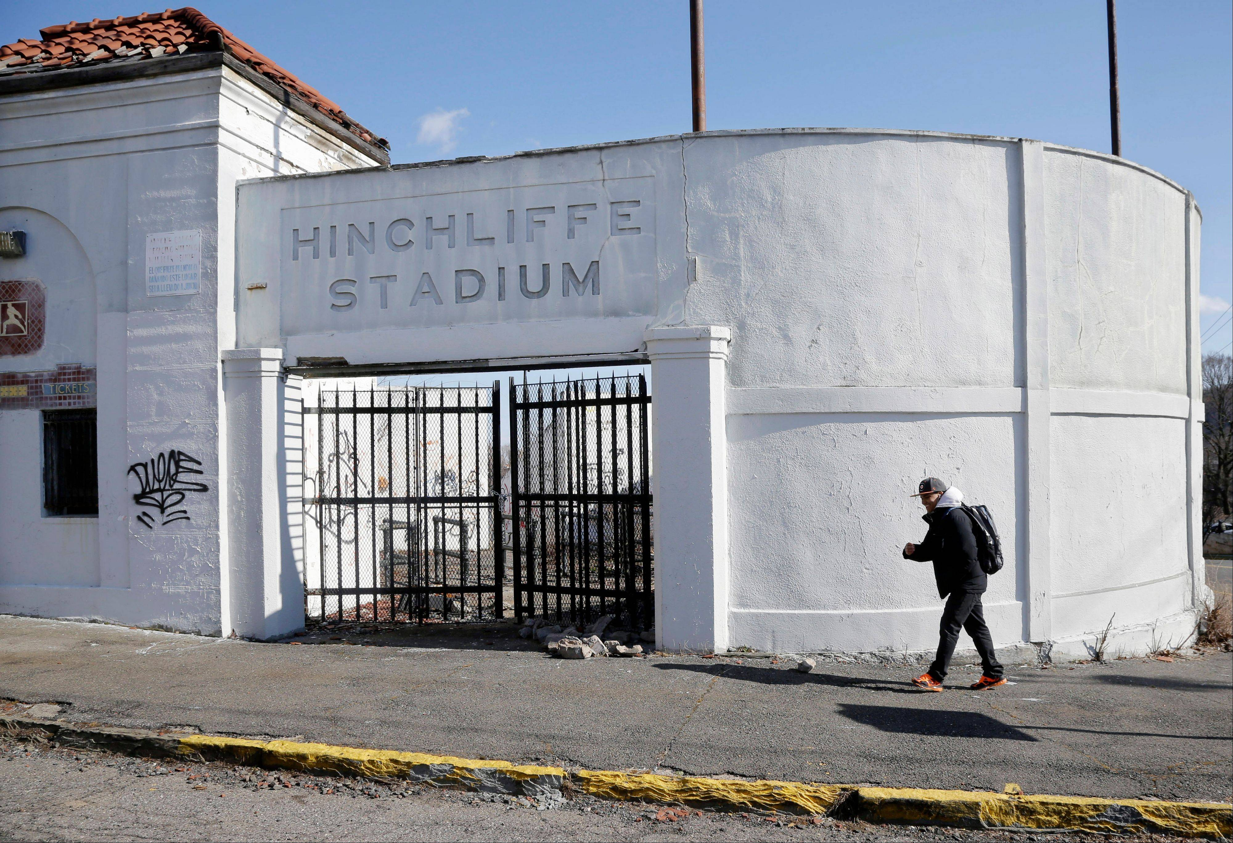 A man walks past an entrance to Hinchliffe Stadium in Paterson, N.J. Hinchliffe, built as a public works project municipal stadium in 1932, now sits in disuse, with trees growing in the graffiti-covered stands and a deteriorated artificial turf surface.