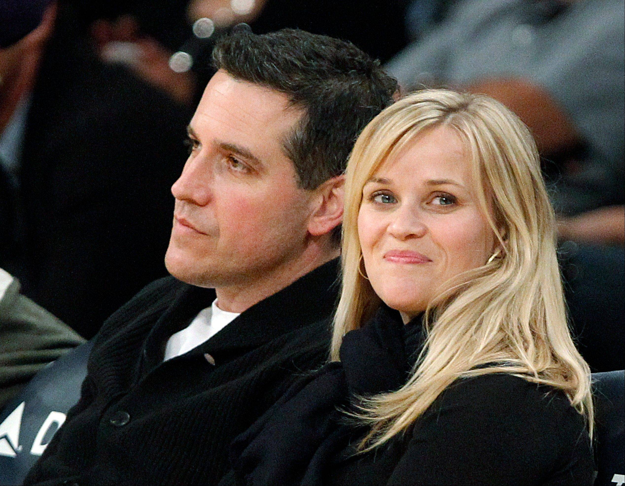 In this Friday, March 8, 2013 file photo, actress Reese Witherspoon and her husband, Jim Toth, watch the Toronto Raptors take on the Los Angeles Lakers in an NBA basketball game in Los Angeles. Police in Georgia say that Witherspoon has been arrested on a disorderly conduct charge after a traffic stop involving her husband in Atlanta. A Georgia State Police incident report says that Witherspoon was arrested early Friday, April 19, 2013, and charged with disorderly conduct. The report says a state trooper observed that a car driven by Toth was failing to stay in its lane. The officer writes that Witherspoon disobeyed multiple orders to stay in the car while he performed a field sobriety test on Toth, accoring to the polcie report.