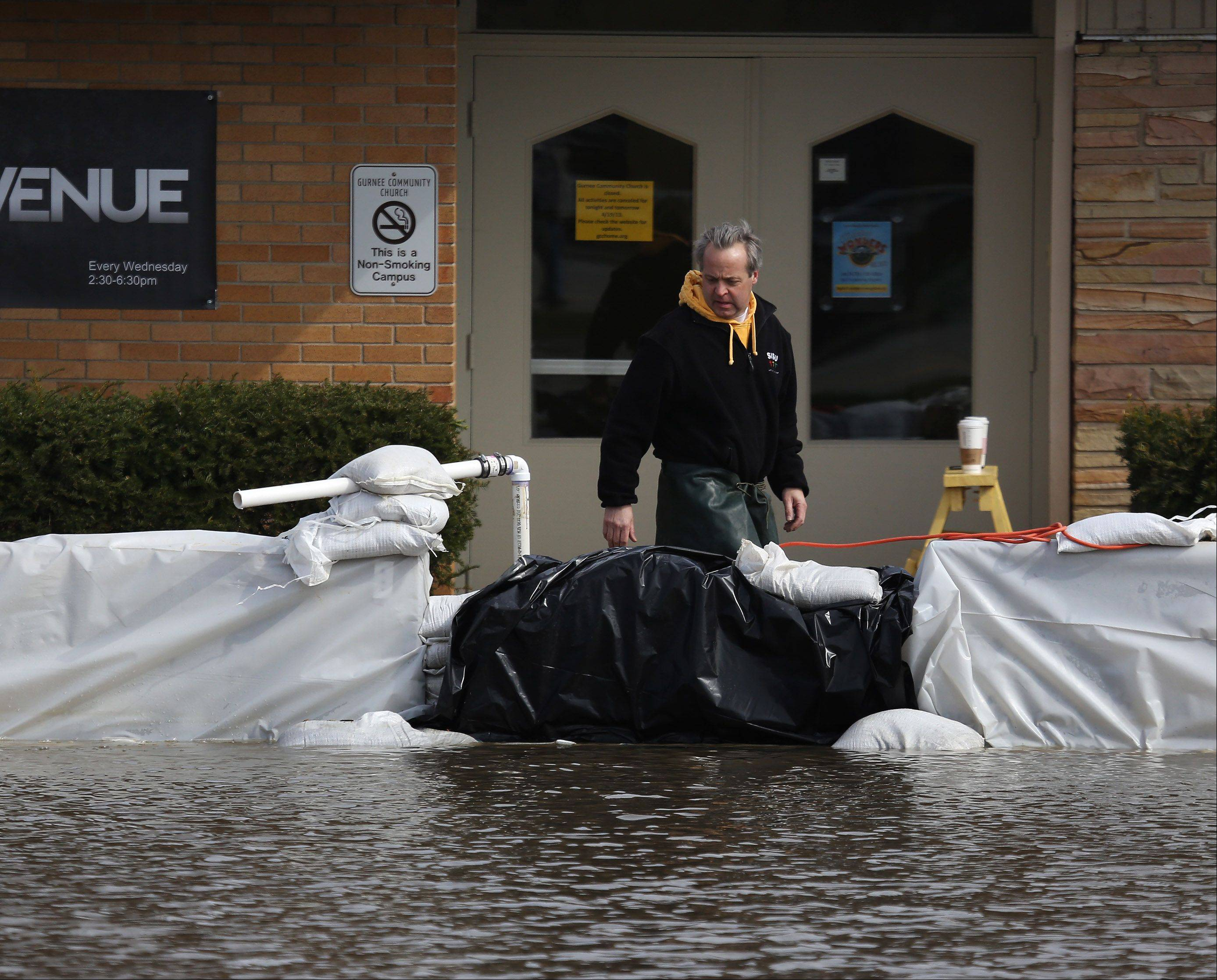 "Volunteer Phil Rosborough checks the sump pumps around Gurnee Community Church after the building was surrounded by flooding from the Des Plaines River Sunday. ""We are keeping the inside dry,"" said Rosborough. ""It is all hands on deck."""