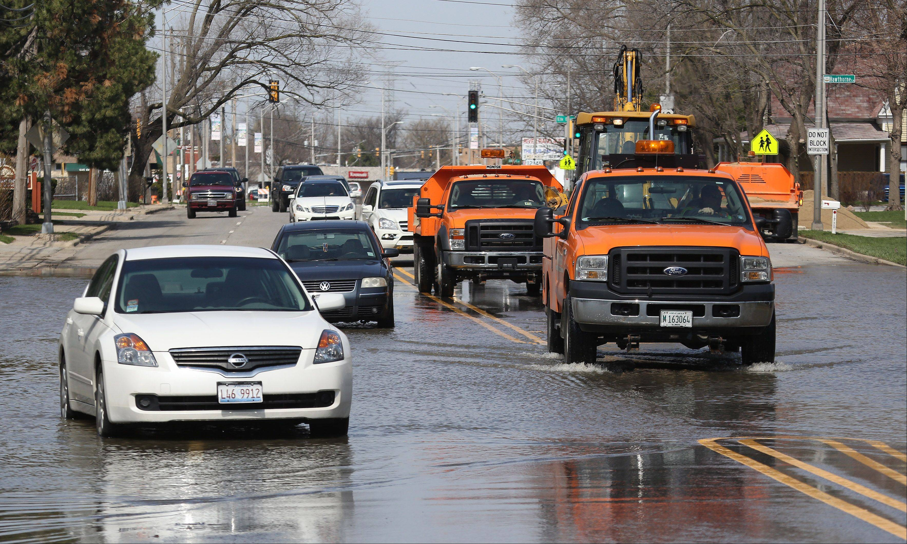 Des Plaines Public Works trucks pass by stranded vehicles along Rand Road after flooding along the Des Plaines River Sunday.