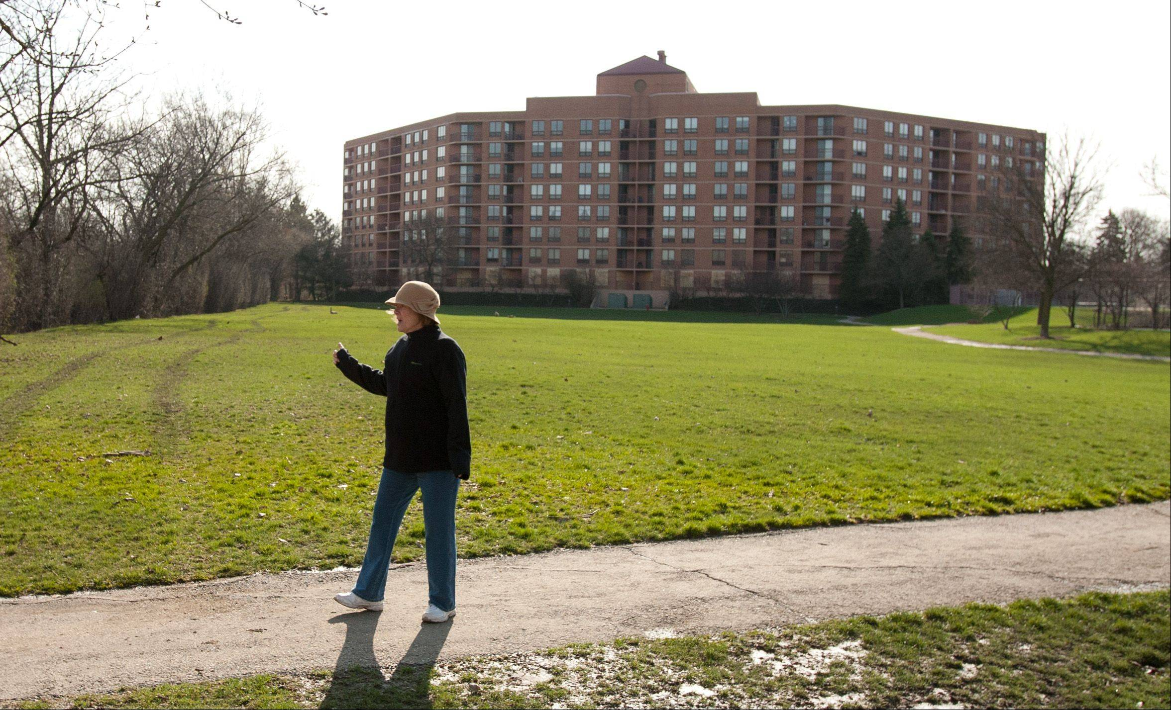 Barbara Joan Boudette points out the height of water in front of one of the Towers of Four Lakes buildings in Lisle. All first-floor windows are boarded up in an effort to prevent looting.