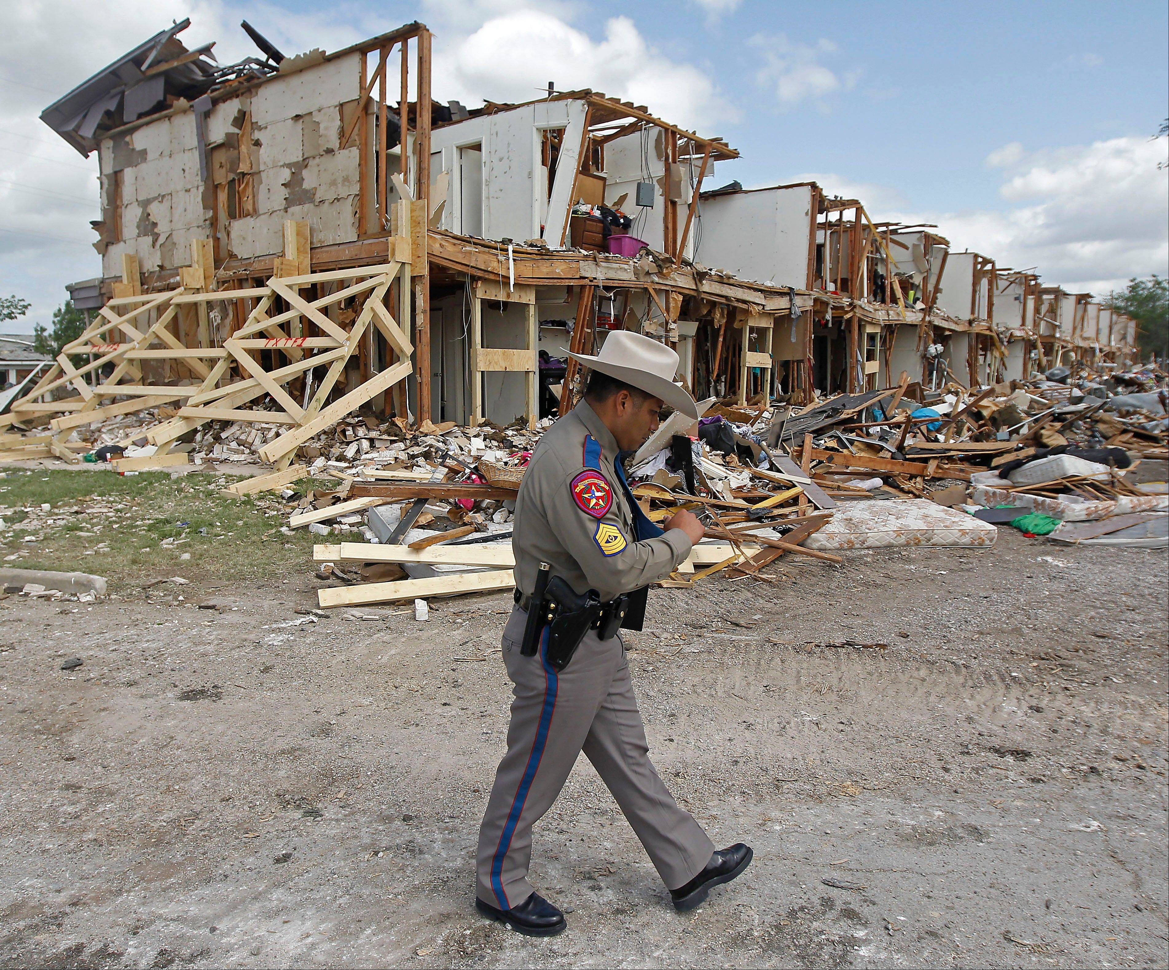 Texas Department of Public Safety Sgt. Jason Reyes walks past a damaged apartment complex, Sunday, April 21, 2013, four days after an explosion at a fertilizer plant in West, Texas. The massive explosion at the West Fertilizer Co. Wednesday night killed 14 people and injured more than 160.