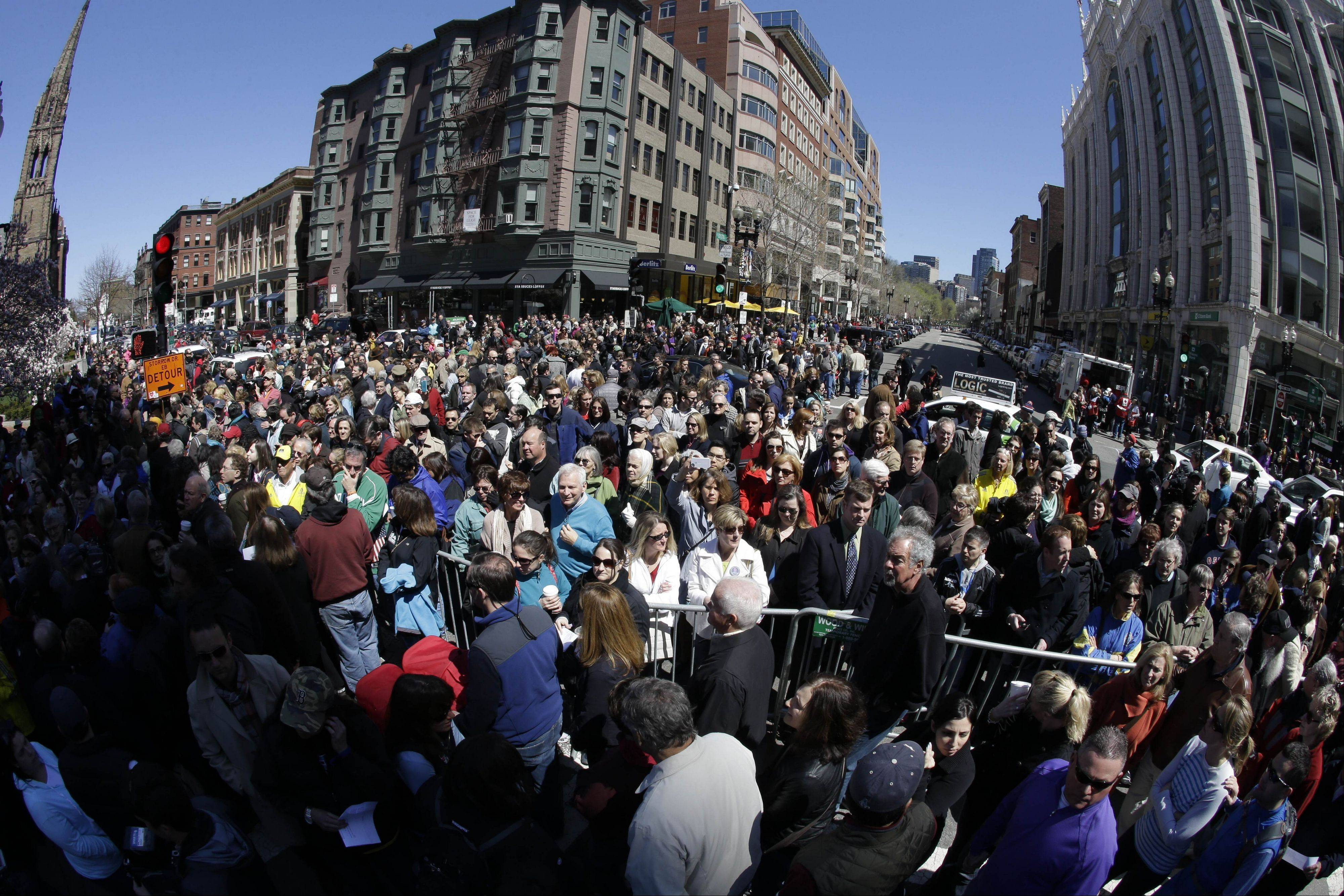 In this photograph made with a fisheye lens, people attend an interfaith service Sunday near a makeshift memorial on Boylston Street, close to the finish line of the Boston Marathon.