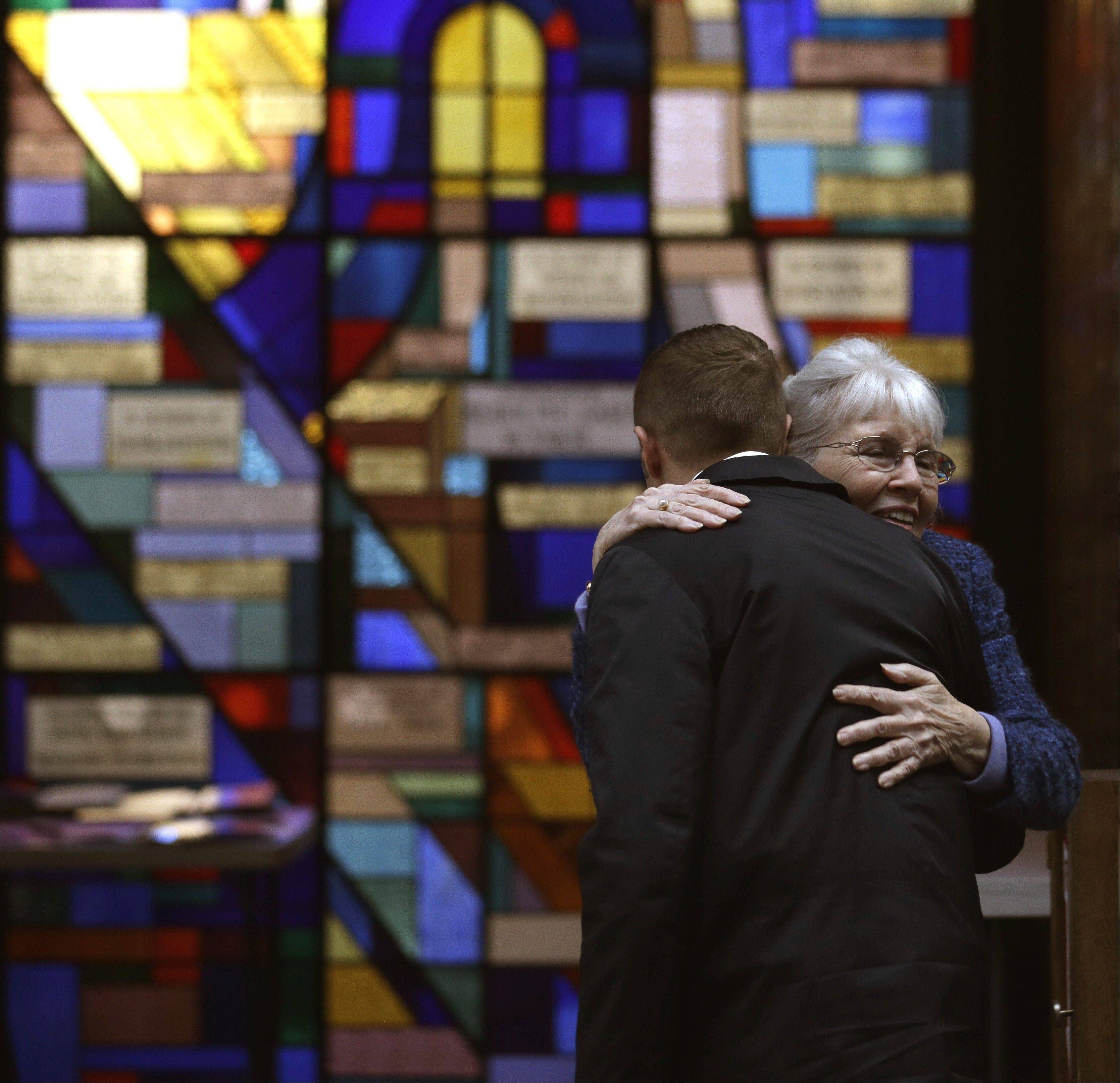 Sue Haff, right, a member of Trinity Episcopal Church in Boston, greets a man arriving at Temple Israel, which allowed the Trinity congregation to hold its Sunday service there.