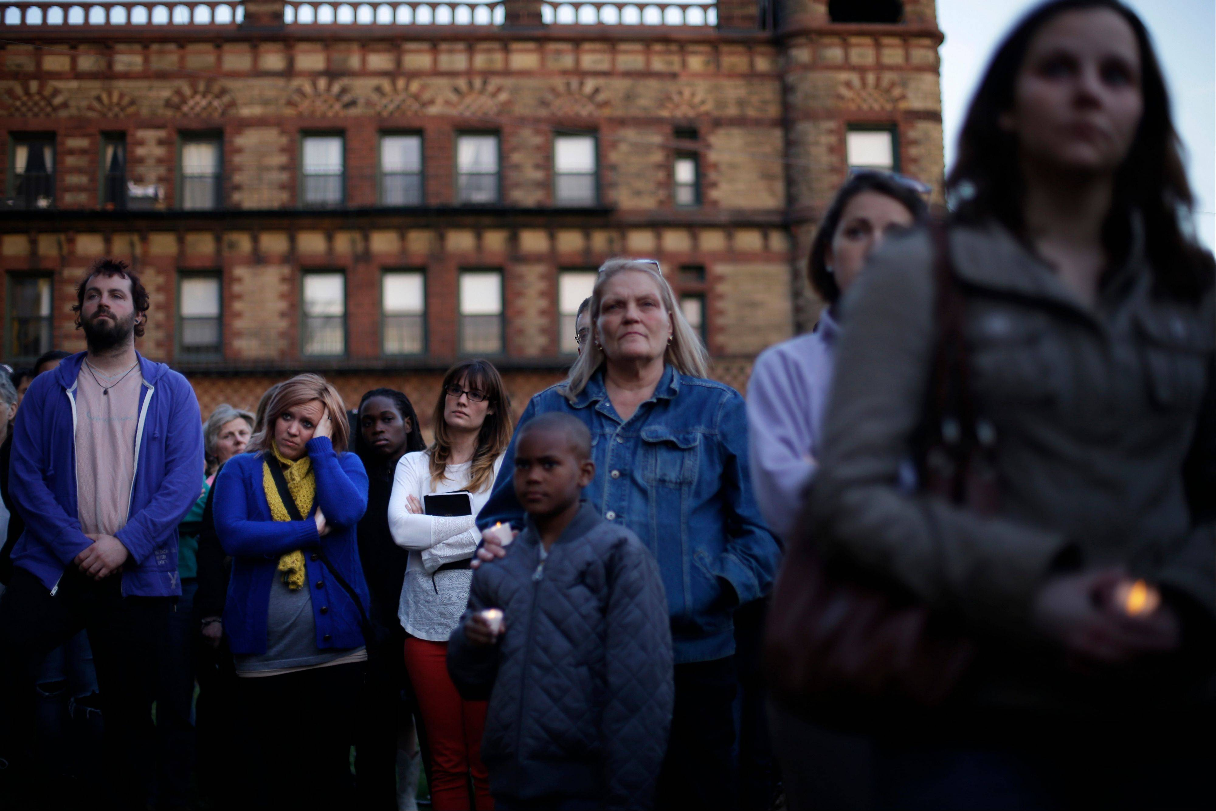 Mourners attend a candlelight vigil at Wednesday at city hall in Cambridge, Mass., in the aftermath of Monday's Boston Marathon explosions, which killed at least three and injured more than 140. .