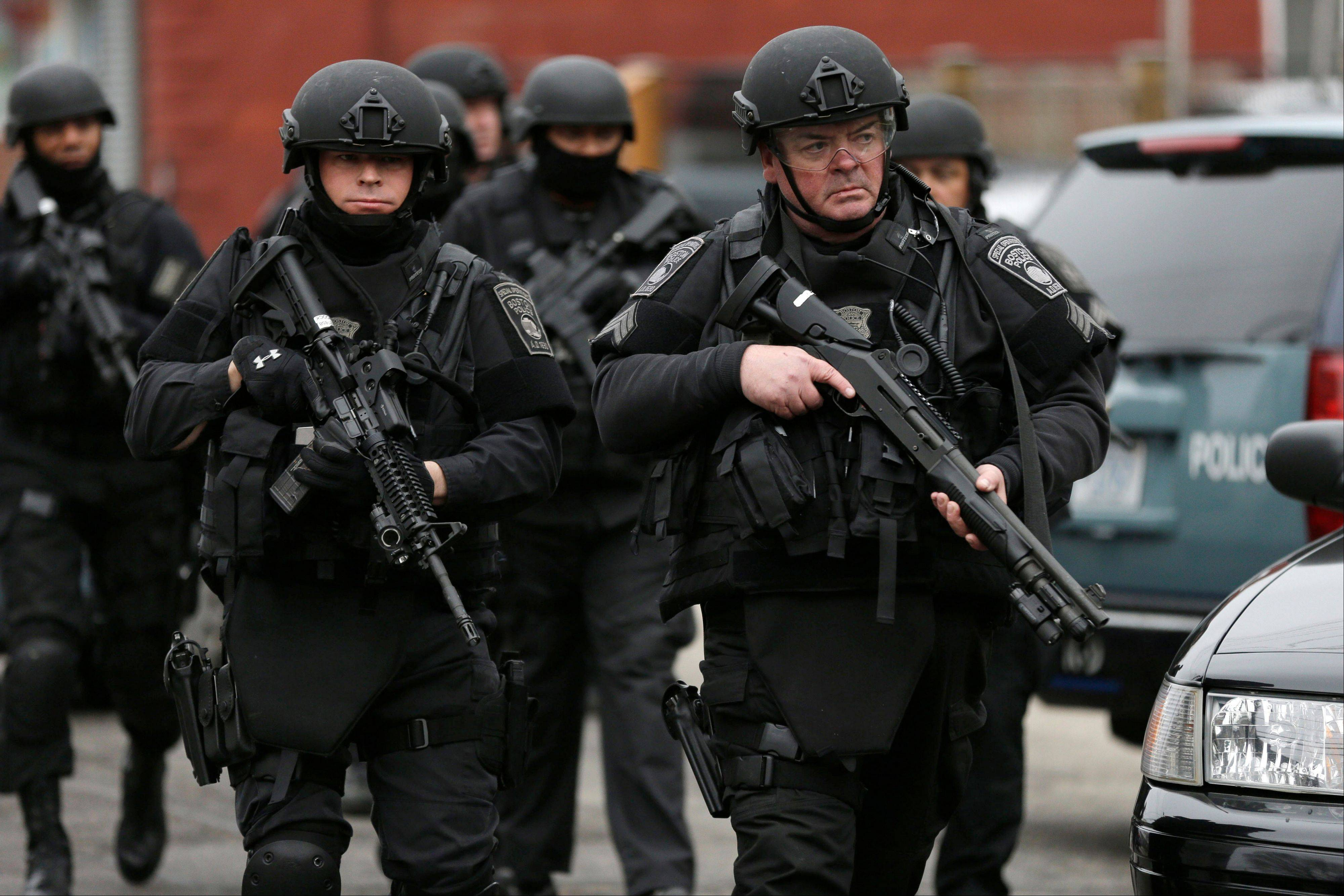 Police in tactical gear conduct a search for a marathon bombing suspect Friday in Watertown, Mass. The bombs that blew up seconds apart near the finish line of the Boston Marathon left the streets spattered with blood and glass, and gaping questions of who chose to attack and why.