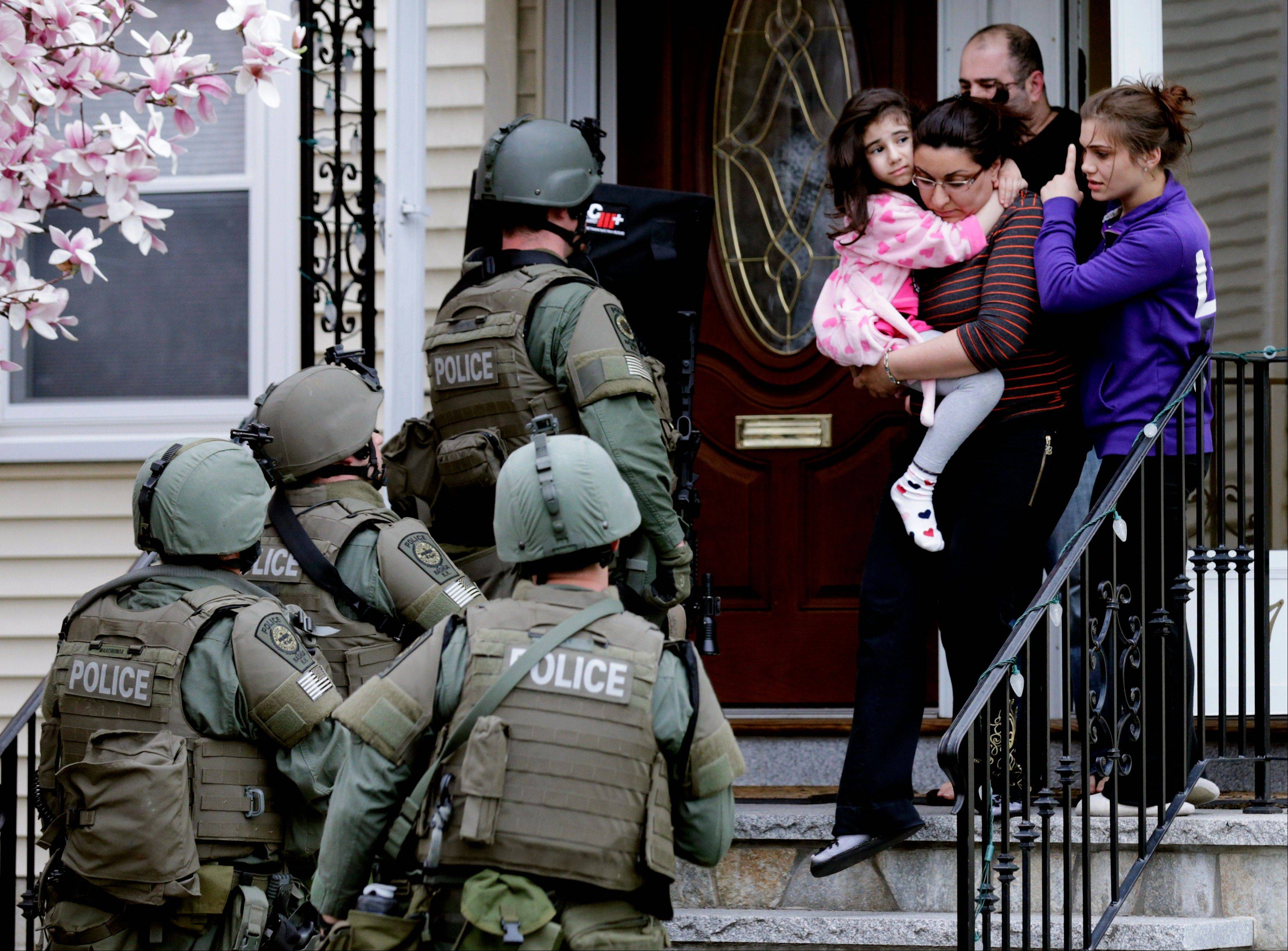 A woman carries a girl from their home as a SWAT team searching for a suspect in the Boston Marathon bombings enters the building Friday in Watertown, Mass.