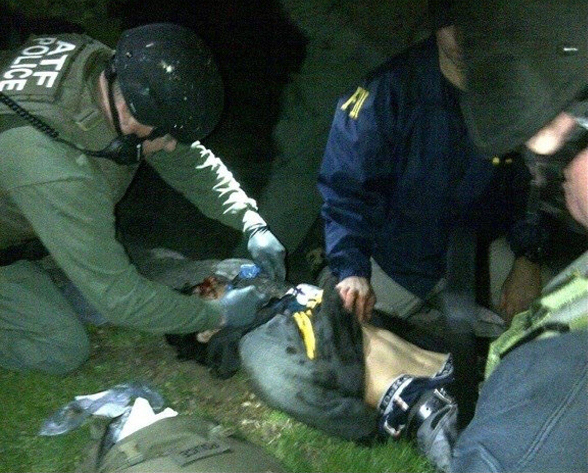 Federal agents check suspect Dzhokhar Tsarnaev for explosives and also give him medical attention Friday night after he was apprehended in Watertown, Mass.