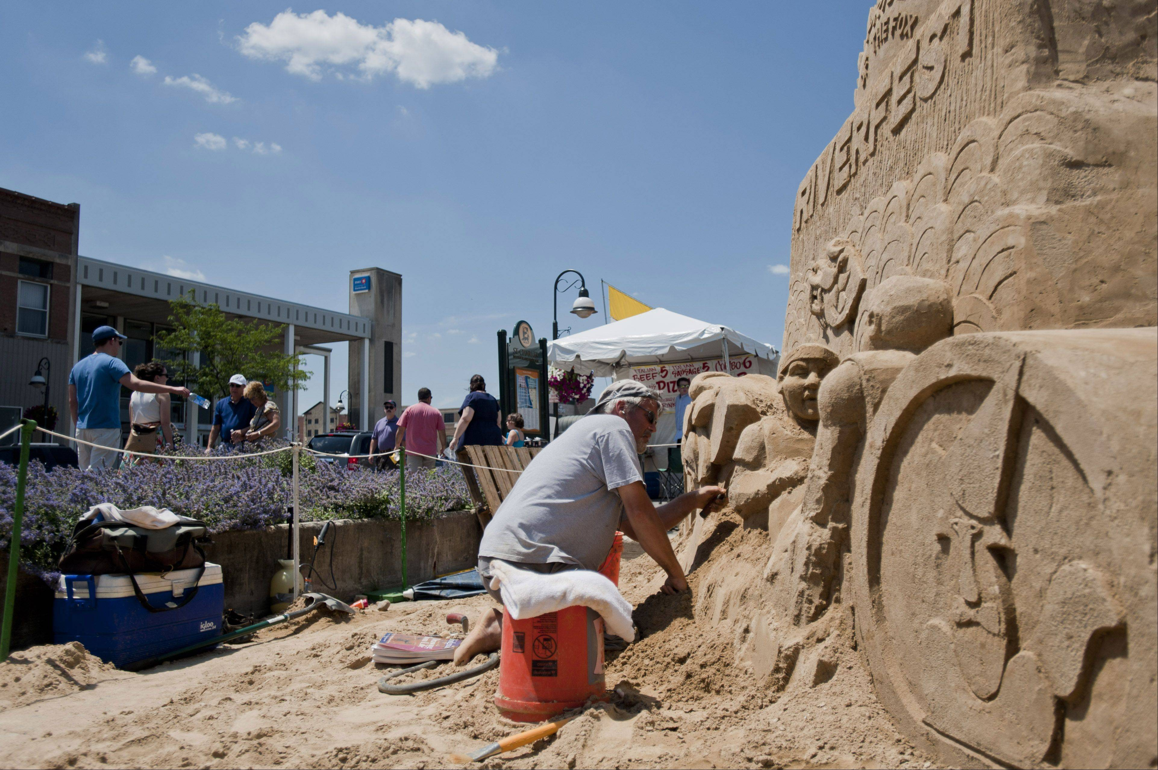 Ted Siebert sculpts a monument to the Pride of the Fox's 30th annual RiverFest last year.