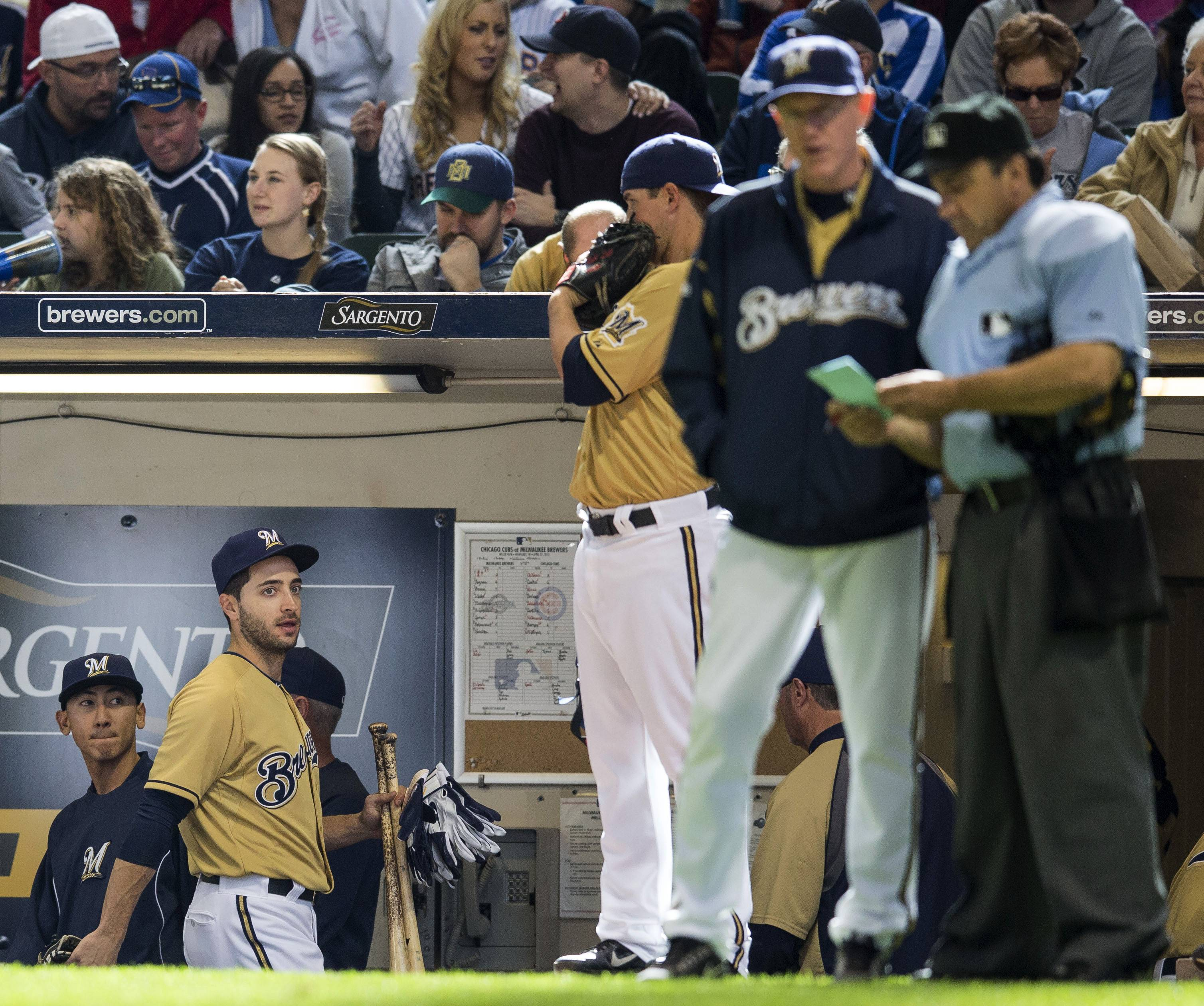 The Brewers' Ryan Braun gathers his equipment and stares at the umpire after his ejection Sunday at home against the Cubs.
