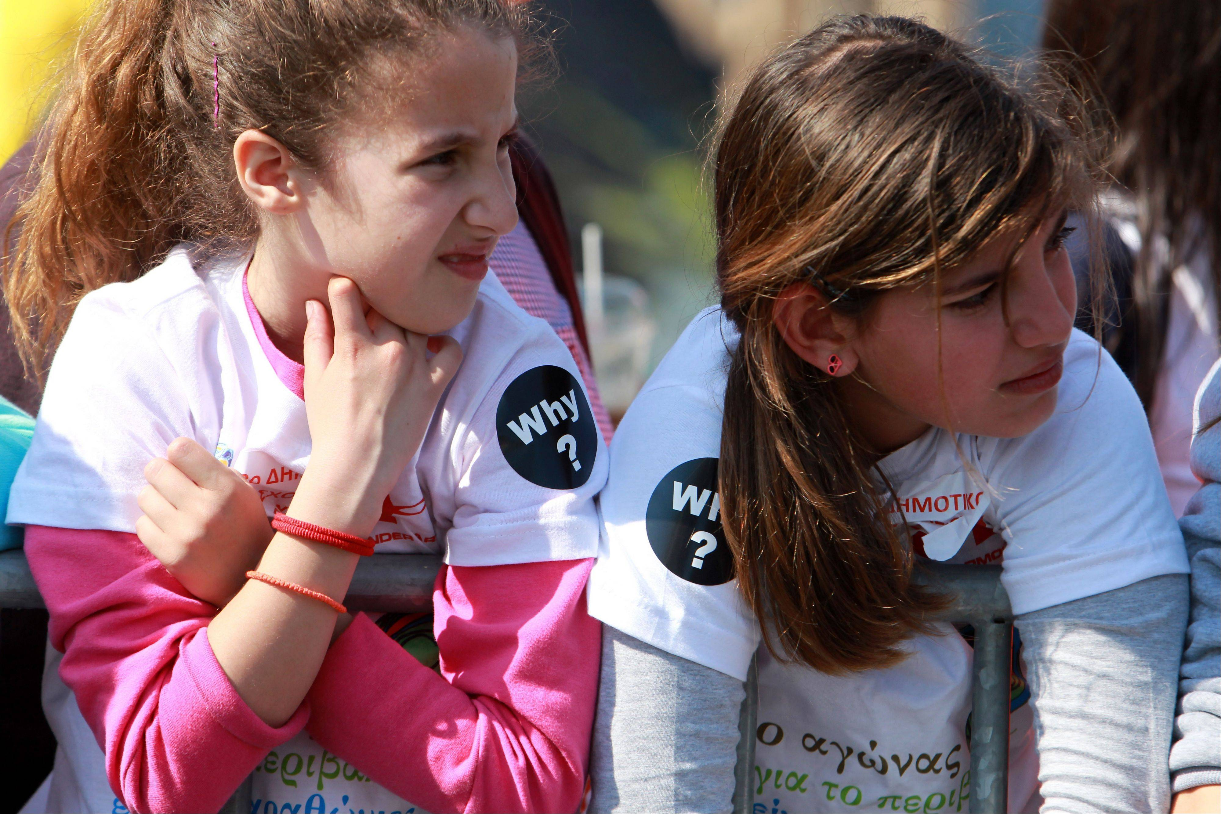 "Children watch the Thessaloniko Marathon in Greece on Sunday. Many participants and spectators wore the message ""Why?"" on their shirts for the victims of the Boston Marathon attacks."