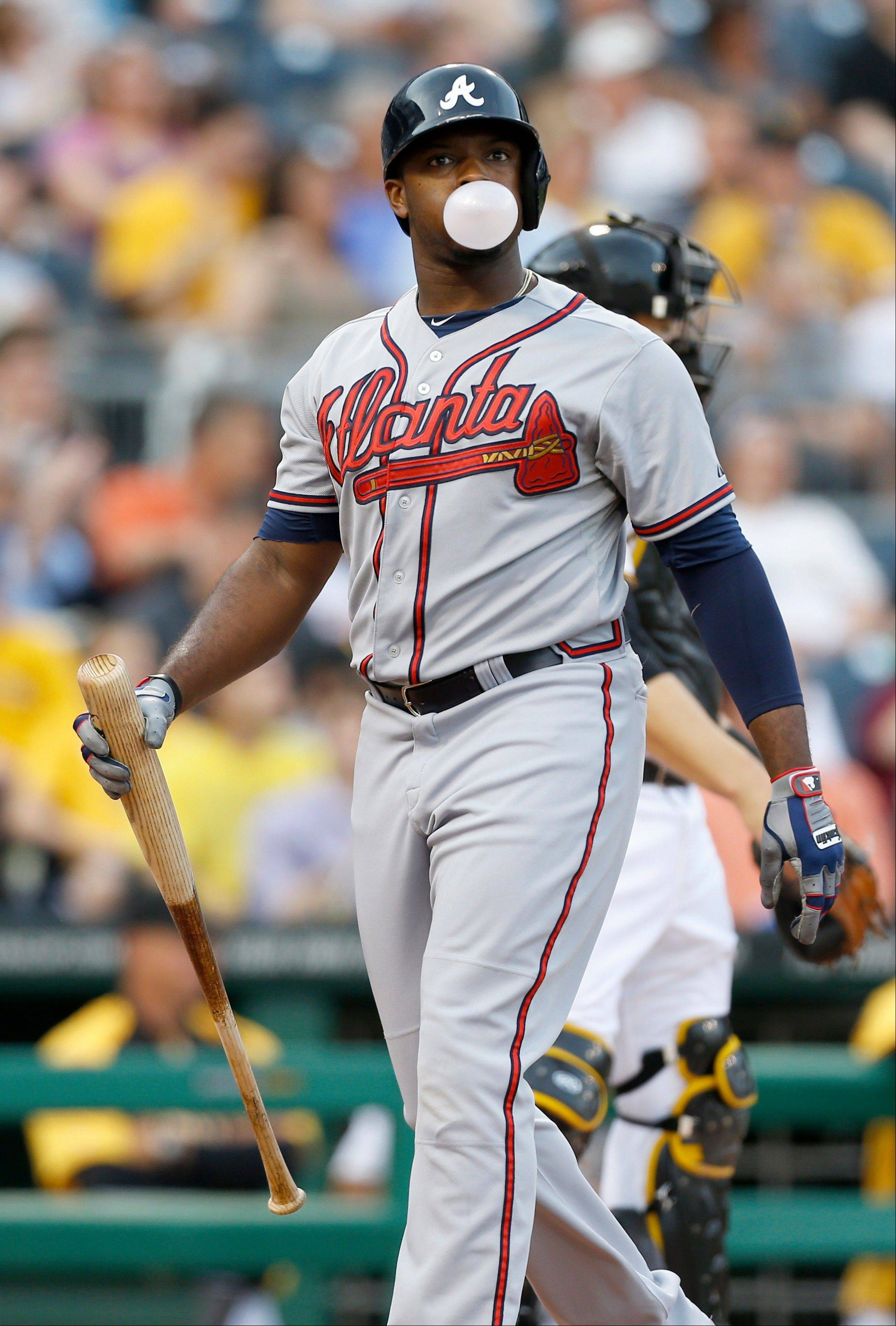 Atlanta Braves' Justin Upton blows a bubblegum bubble on his way back to the dugout after striking out in the first inning of a baseball game against the Pittsburgh Pirates, Thursday, April 18, 2013, in Pittsburgh.