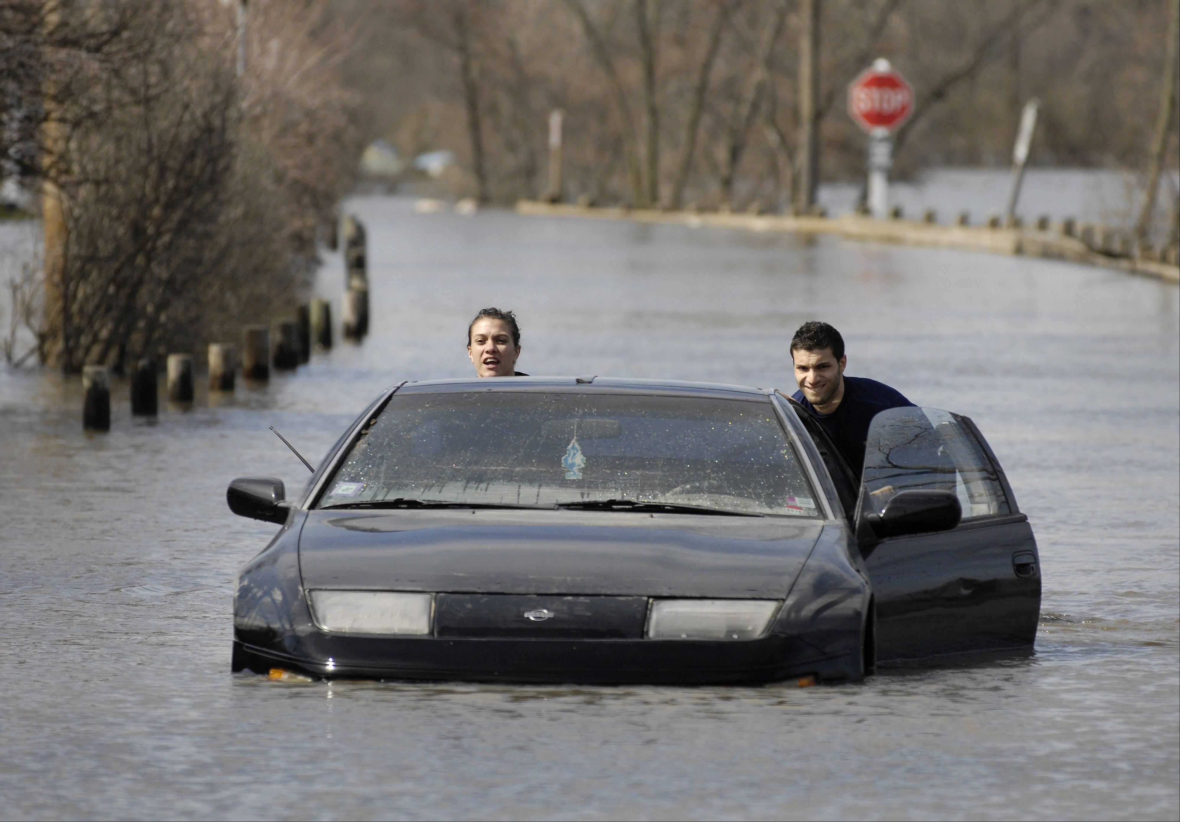 Ashley and Victor Atalla push the second of their two cars out of floodwaters Monday at Four Lakes subdivision in Lisle. The Atallas were forced to park in a low-lying area after the raised parking lot at the Towers at Four Lakes affiliated with their apartment building was full.