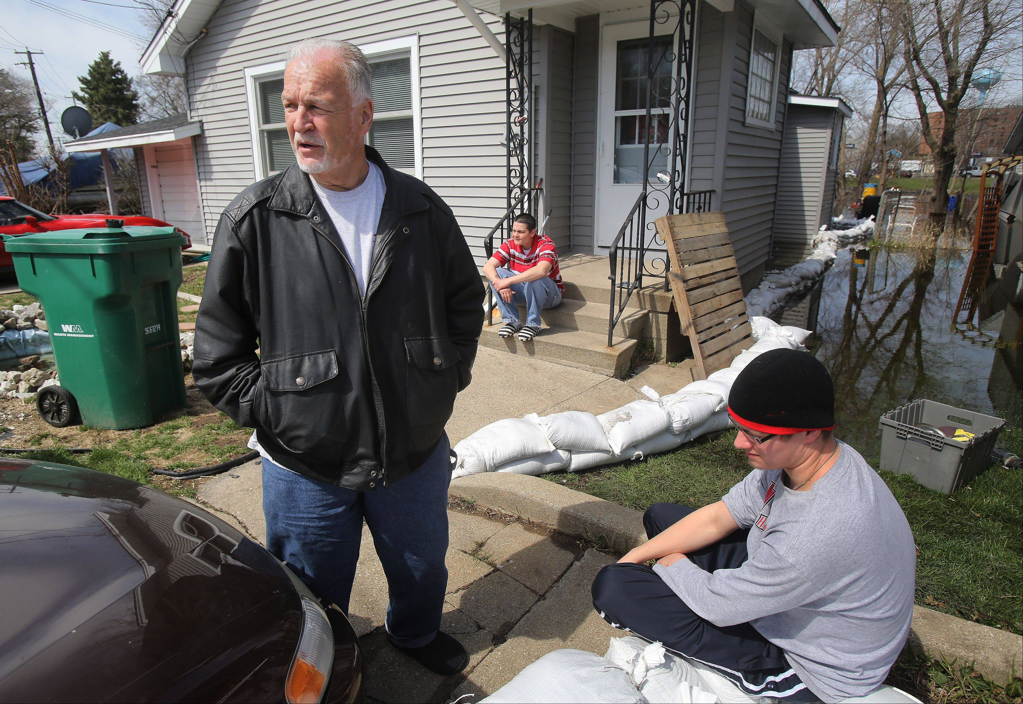 Fox Lake resident Ed Sikora discusses the affects of flooding on his home in Fox Lake on Monday. Diane Hristov is sitting on the porch and neighbor Ryan Jaworek is right.