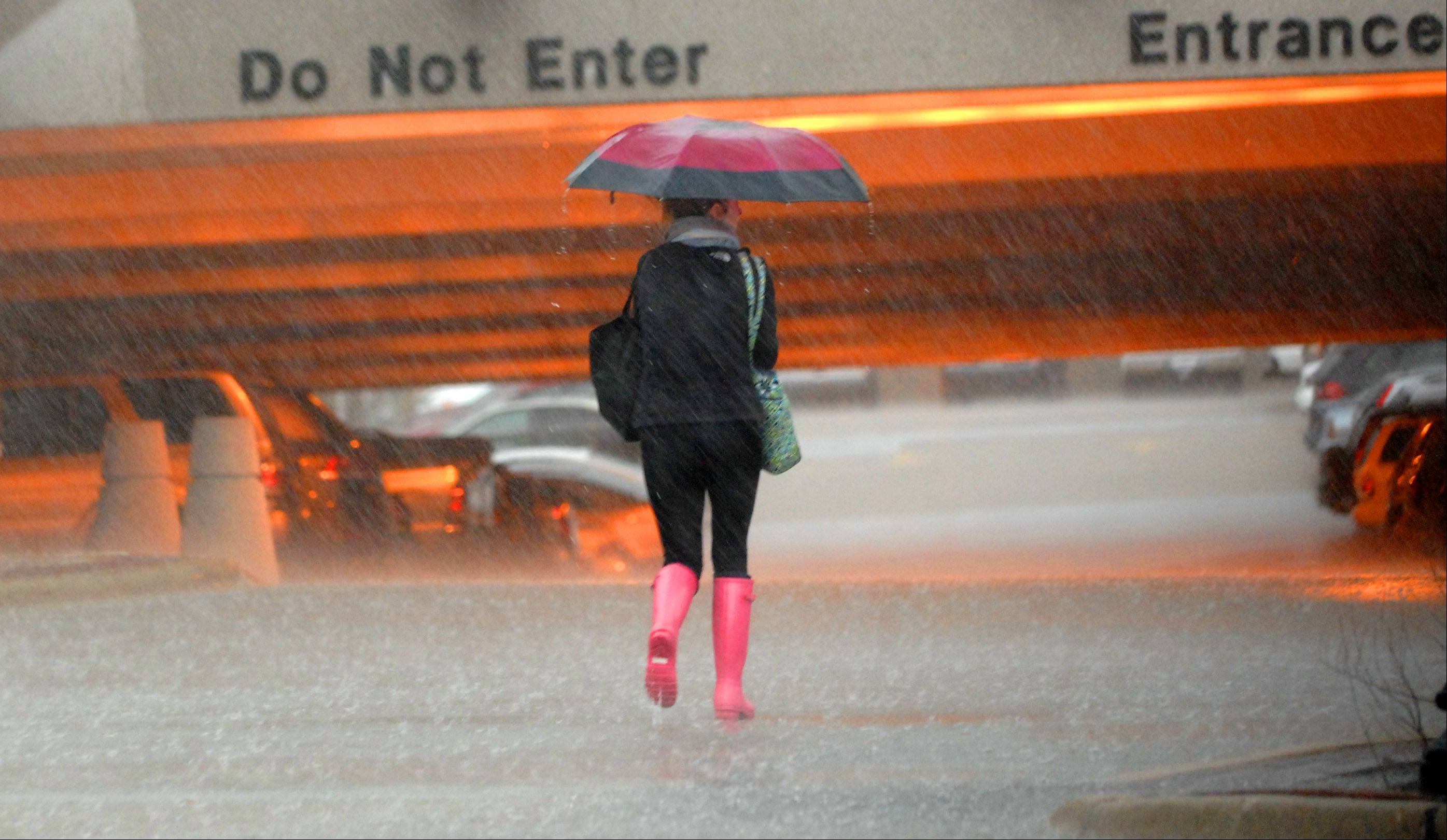A commuter tries to stay dry after getting off a Metra train and heading to the parking garage in Geneva during Wednesday�s afternoon storms.