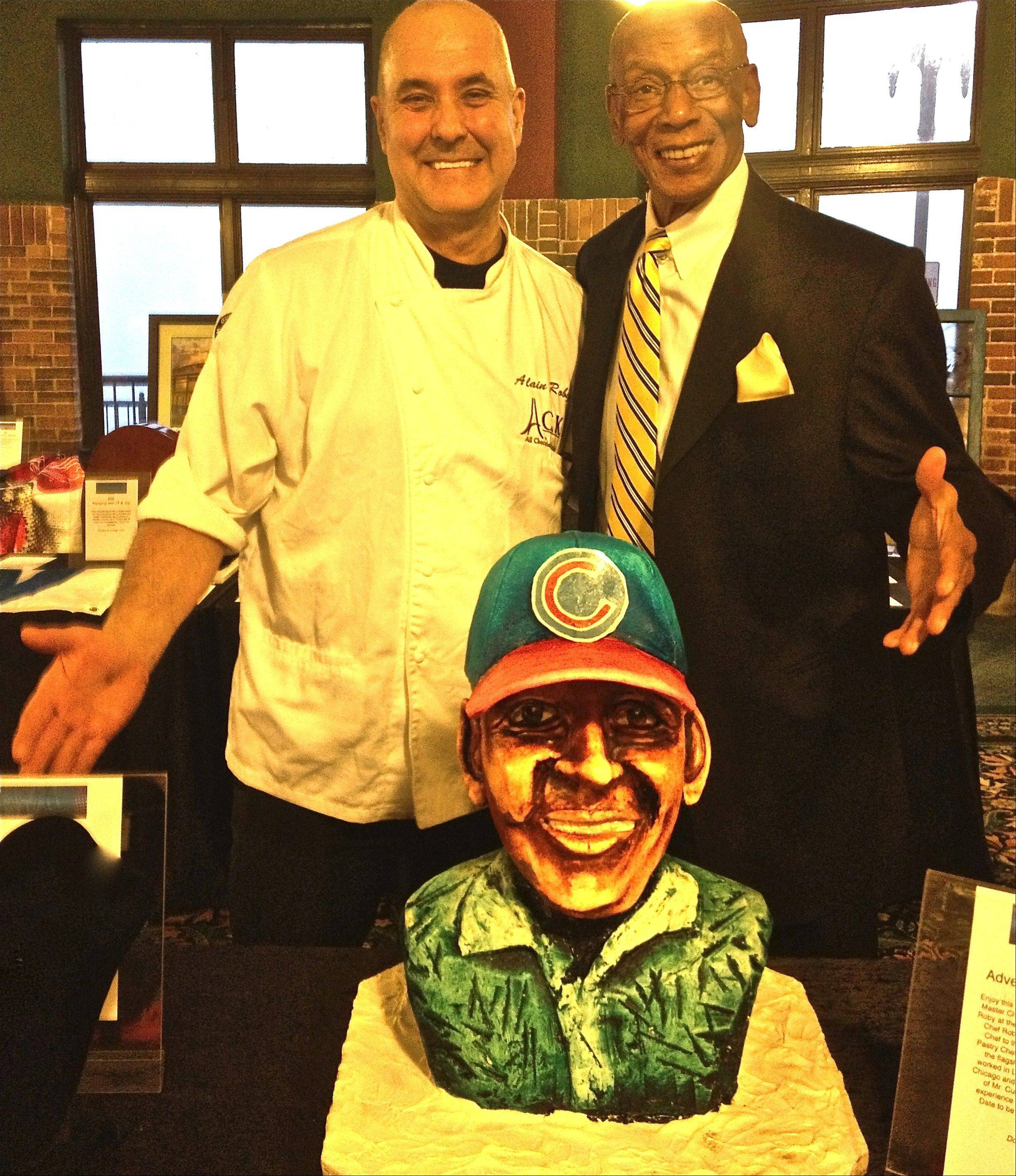 Chef Alain Roby, left, and Cub legend Ernie Banks pose in front of a bust created from chocolate to benefit the Cubs Charities.