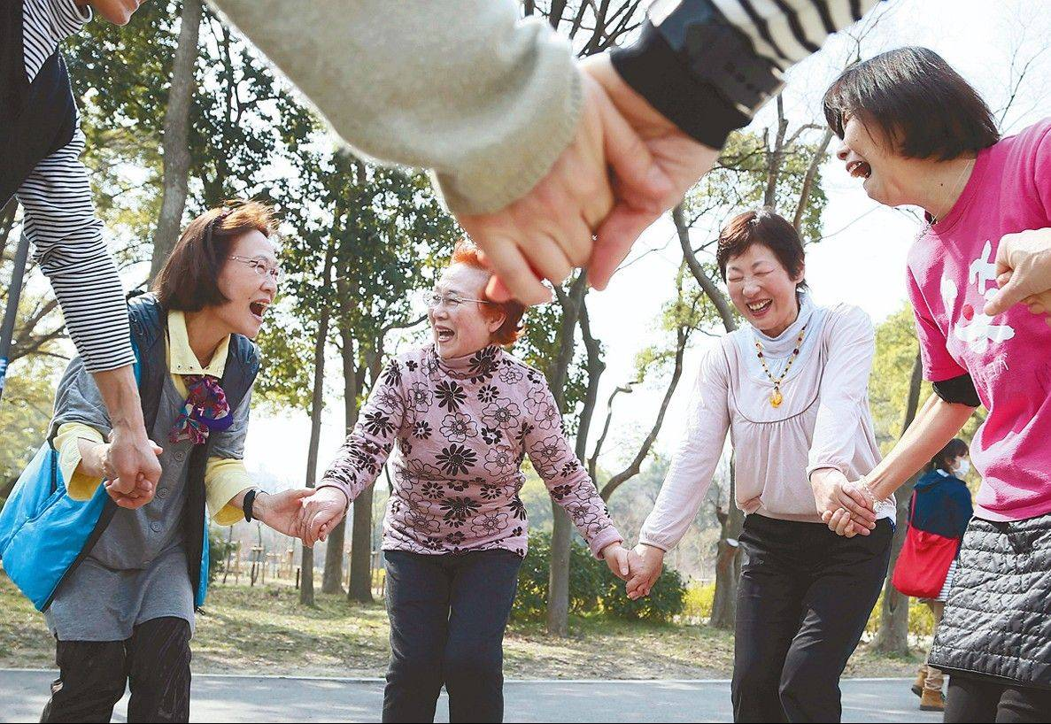 Rikako Ueda, right, instructs a group of women in a laughter yoga session at Osaka Castle Park in Osaka, Japan.