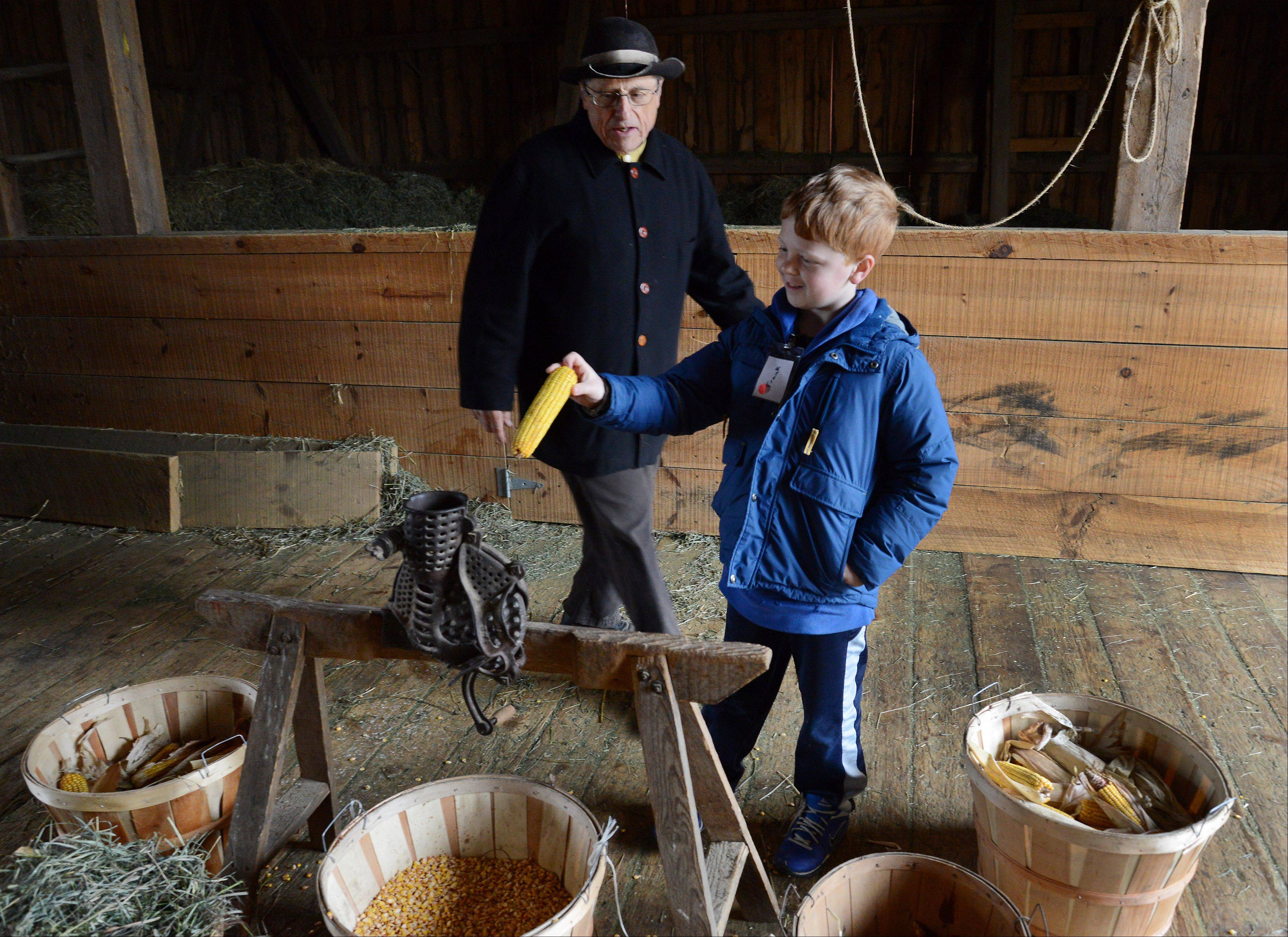 Retiree Dick Ruffalo shows third-grader Frank Eleftheriou of Kimball Hill Elementary School how to mill corn at Spring Valley Nature Center in Schaumburg.