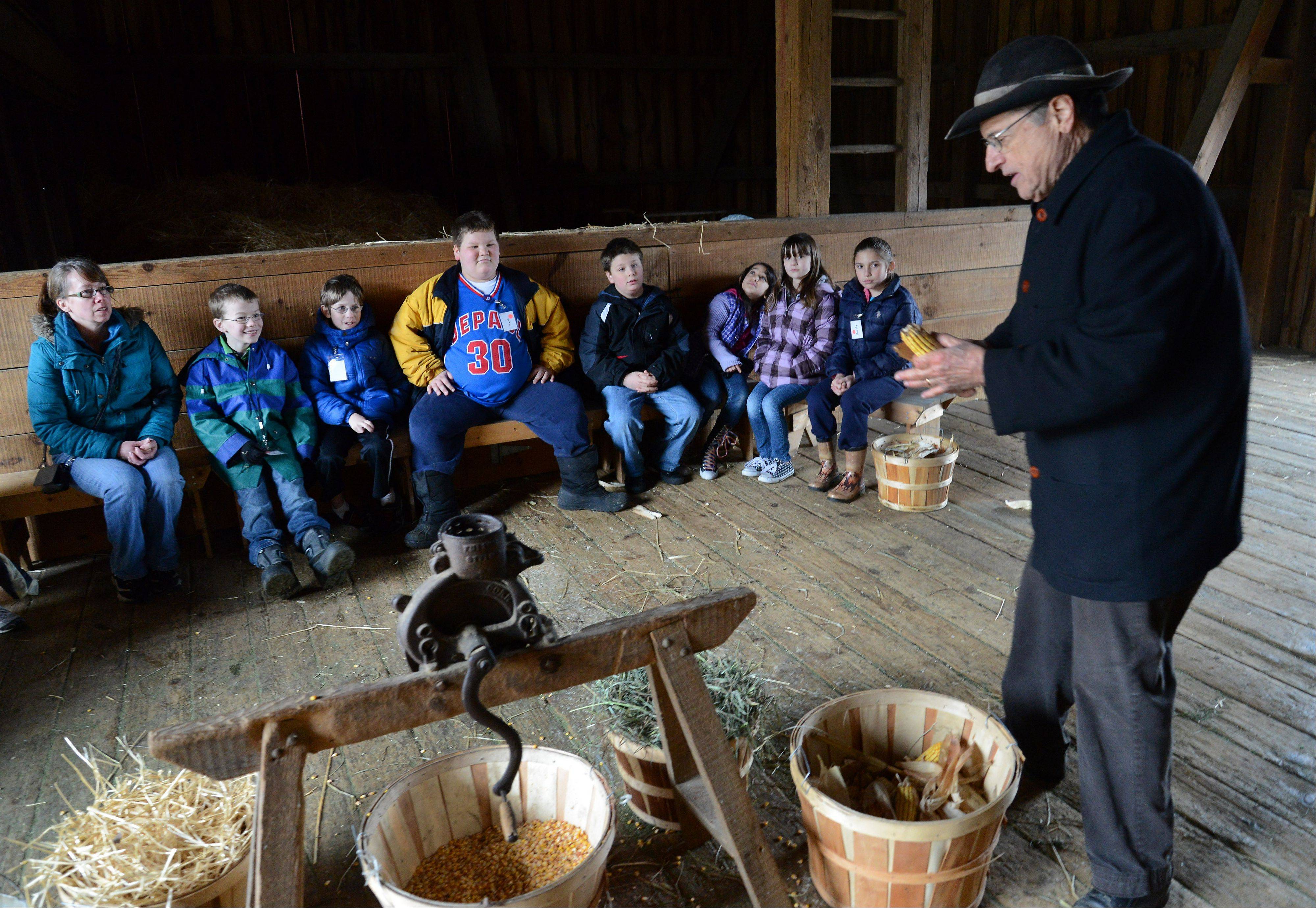 Retiree Dick Ruffalo teaches Kimball Hill Elementary School third-graders about milling corn at Spring Valley Nature Center in Schaumburg.