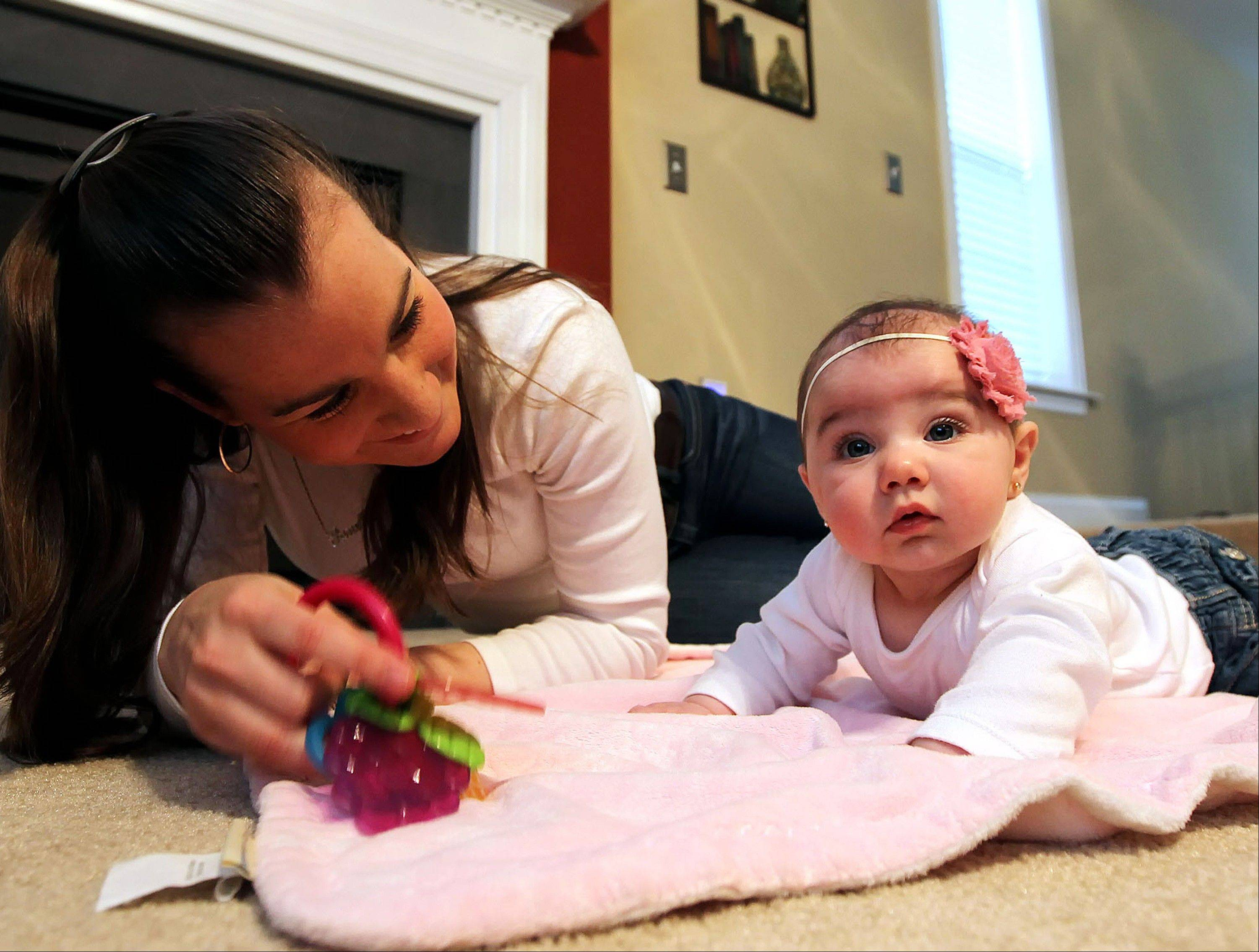 Janelle Valore plays with her daughter, Alena Valore, 5 months, who has colic, at their home in Mt. Joy, Pa. The distressing nonstop crying of colic in babies is often blamed on tummy trouble. But now a new study says the problem could be linked with migraine headaches in at least some infants.