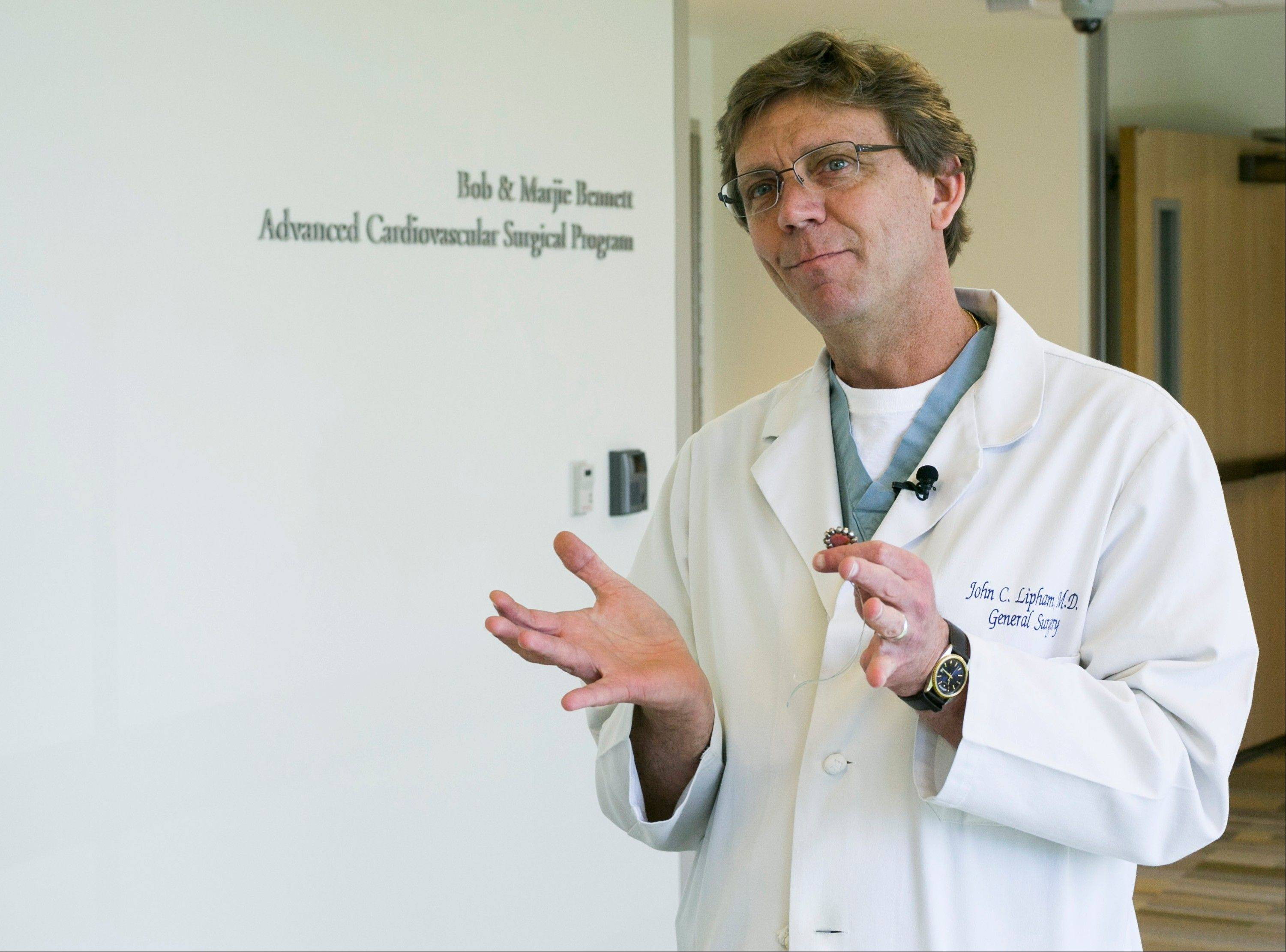 Surgeon Dr. John Lipham talks about the new Linx device, in his right hand, at the Hoag Memorial Hospital Presbyterian in Newport Beach, Calif. The bracelet-like device is implanted around a weak muscle at the base of the throat that doesn't close.
