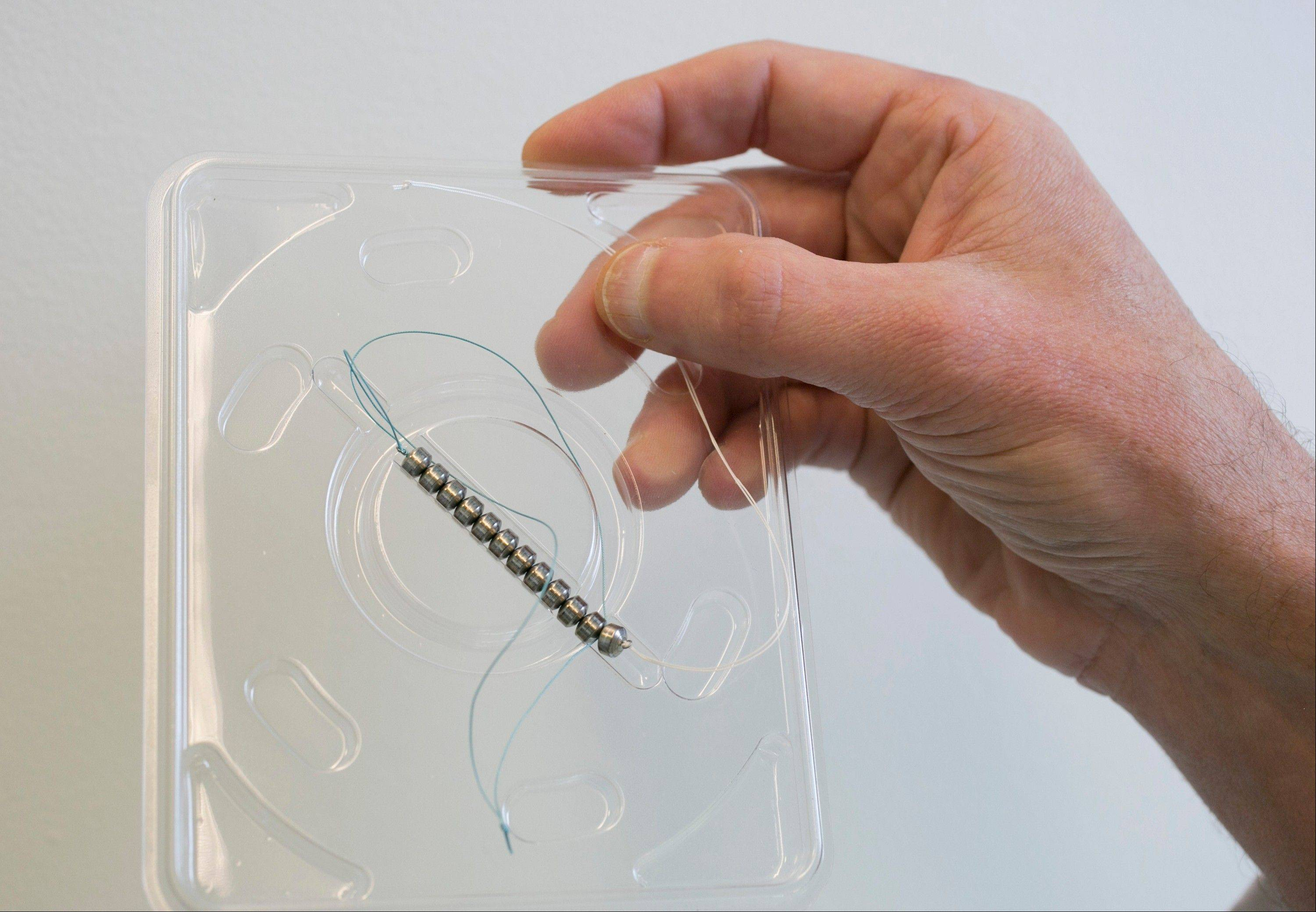 Surgeon Dr. John Lipham holds a sample LINX device, which is designed to help the esophageal sphincter stay closed to stop the reflux. It uses a small, flexible band of beads with each bead carrying a magnet inside.