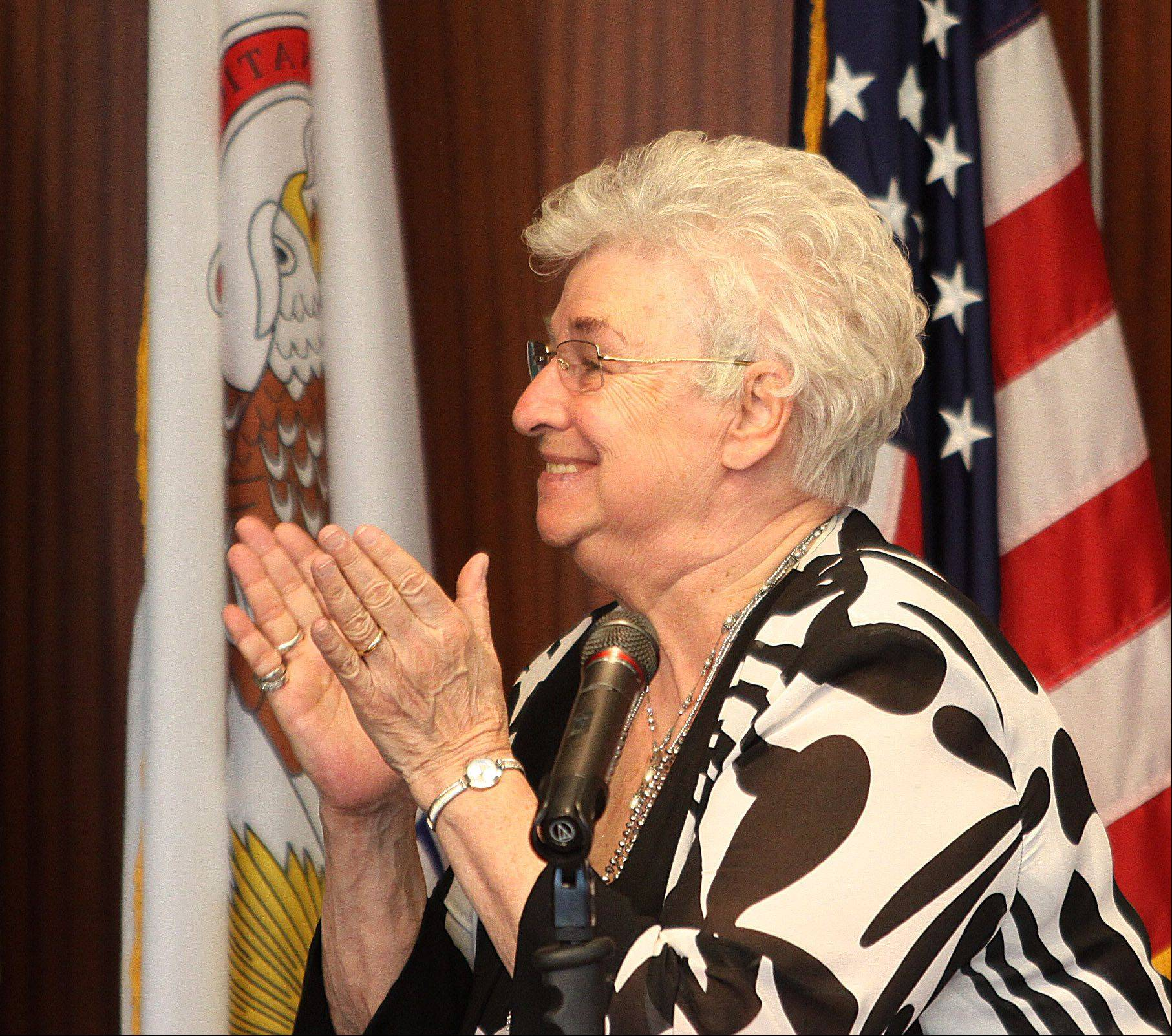 At her final board meeting as Wheeling village president, Judy Abruscato applauds the White Tiger Martial Arts Center on Monday for its success at the Illinois State Taekwondo competition.