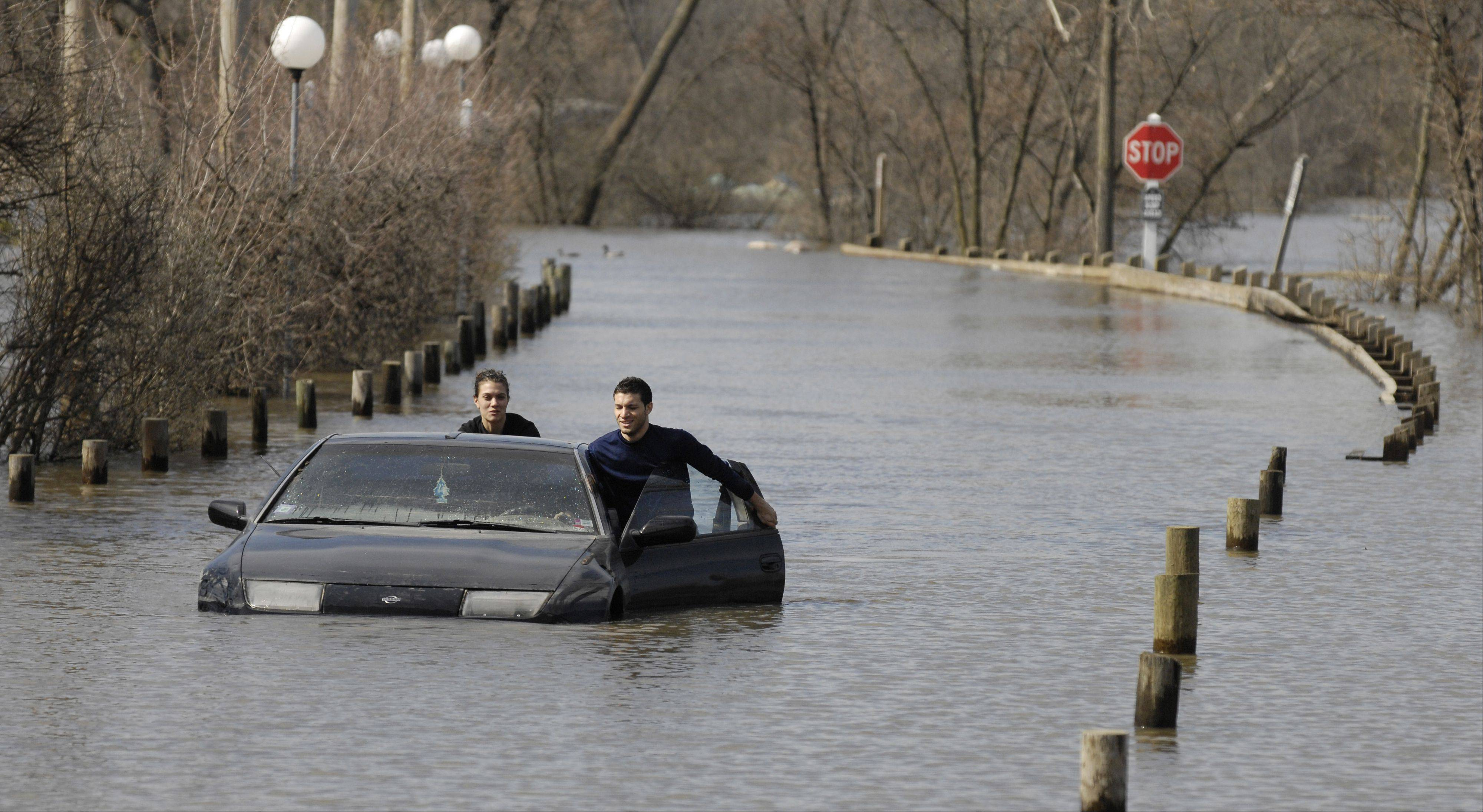 Ashley and Victor Atalla push the second of their two cars out of floodwaters at Four Lakes in Lisle.