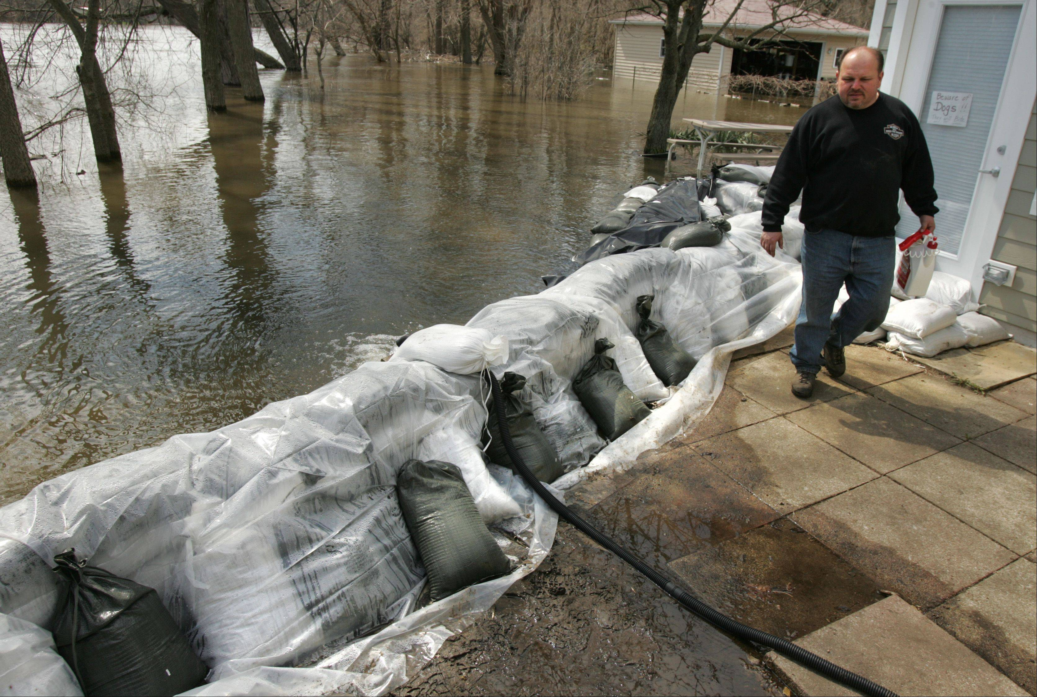 Algonquin resident Tony Angarola inspects the sandbag wall currently holding back about a foot of water from the Fox River Monday morning. The village has distributed more than 14,000 sandbags to its residents, an official said.