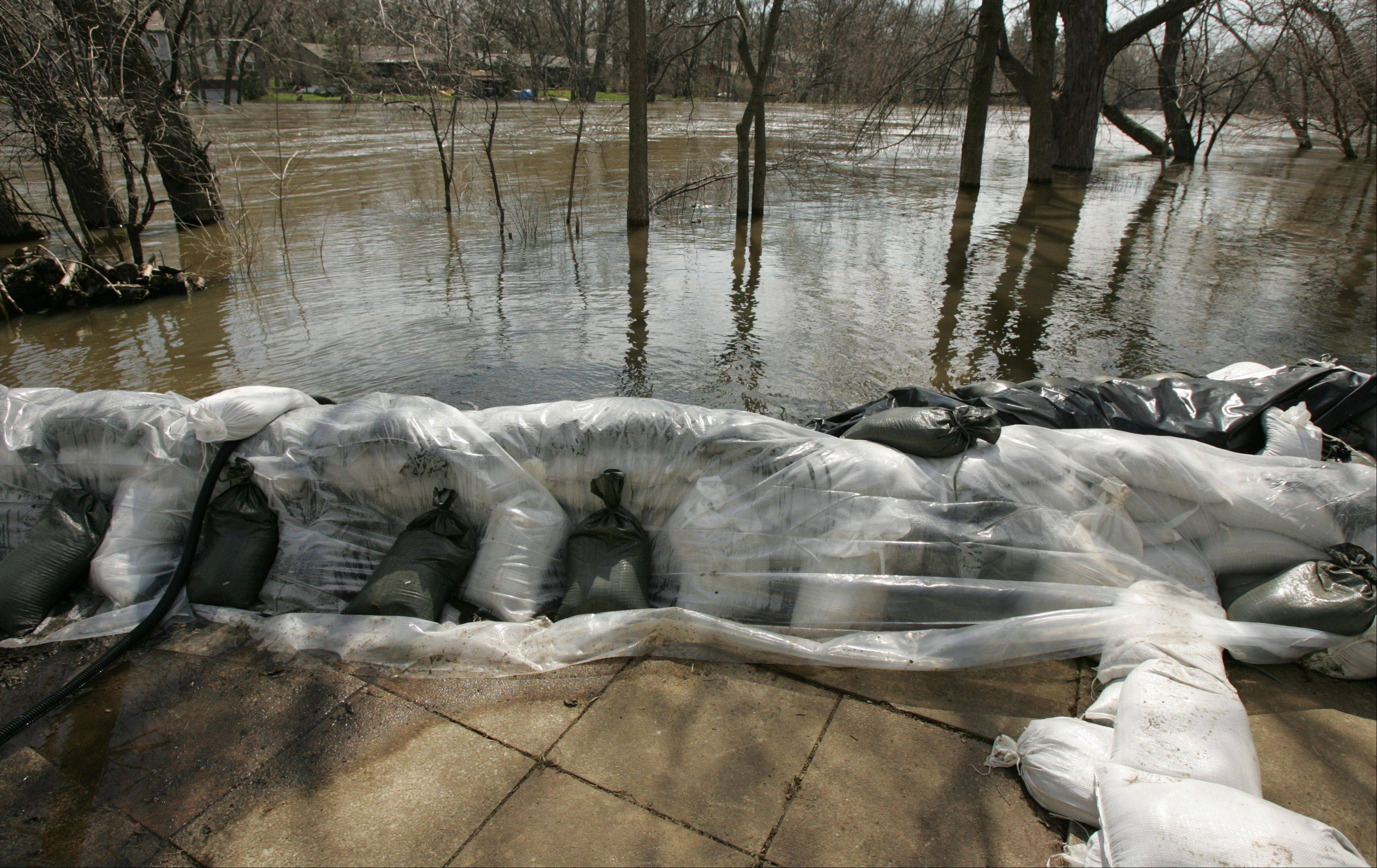 A wall of sandbags is keeping the Fox River at bay Monday behind Tony Angarola's property in Algonquin, and he's hoping the rain this week is minimal to keep the level from rising further.