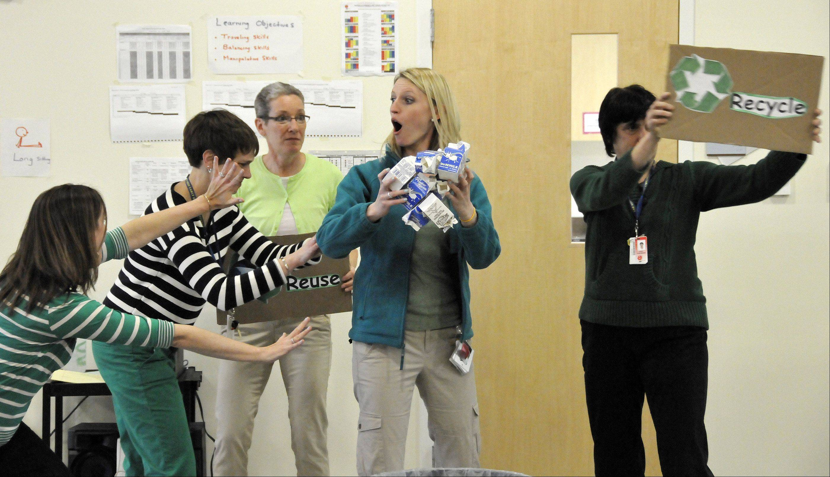 Ann Reid Early Childhood Center teachers perform a skit about recycling and sing a song about the three R's, reduce, reuse and recycle, during Monday's Earth Day flag presentation.