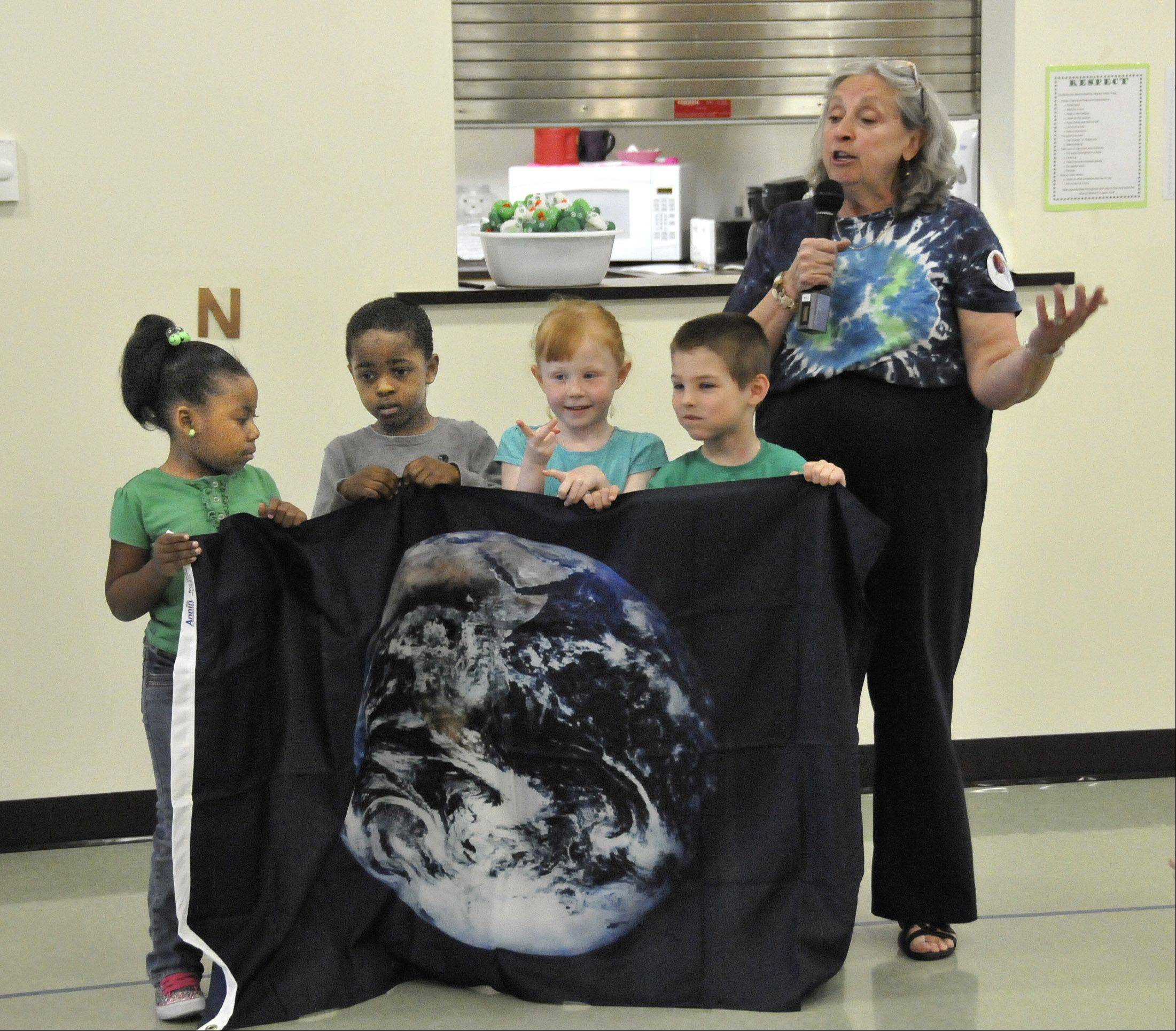 SCARCE representative Kay McKeen presents an Earth Day flag Monday to the Ann Reid Early Childhood Center in Naperville. Preschoolers, including Jayce Fox, Amarris Lofton, Colette McInerny and Max Henson helped hold the flag during the presentation.