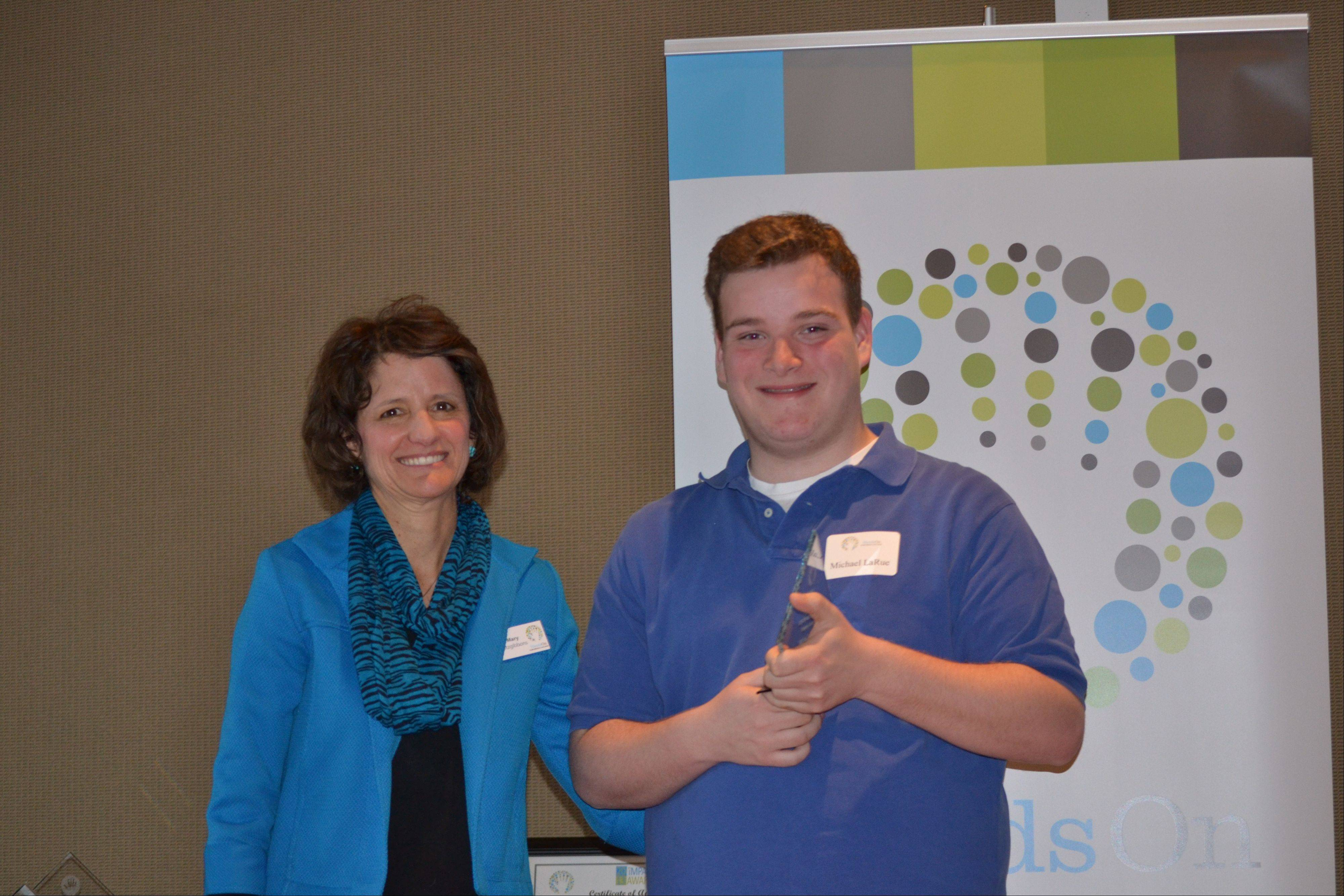 Michael LaRue receives his Emerging Young Leader award from Mary Fitzgibbons, executive director of HandsOn Suburban Chicago.