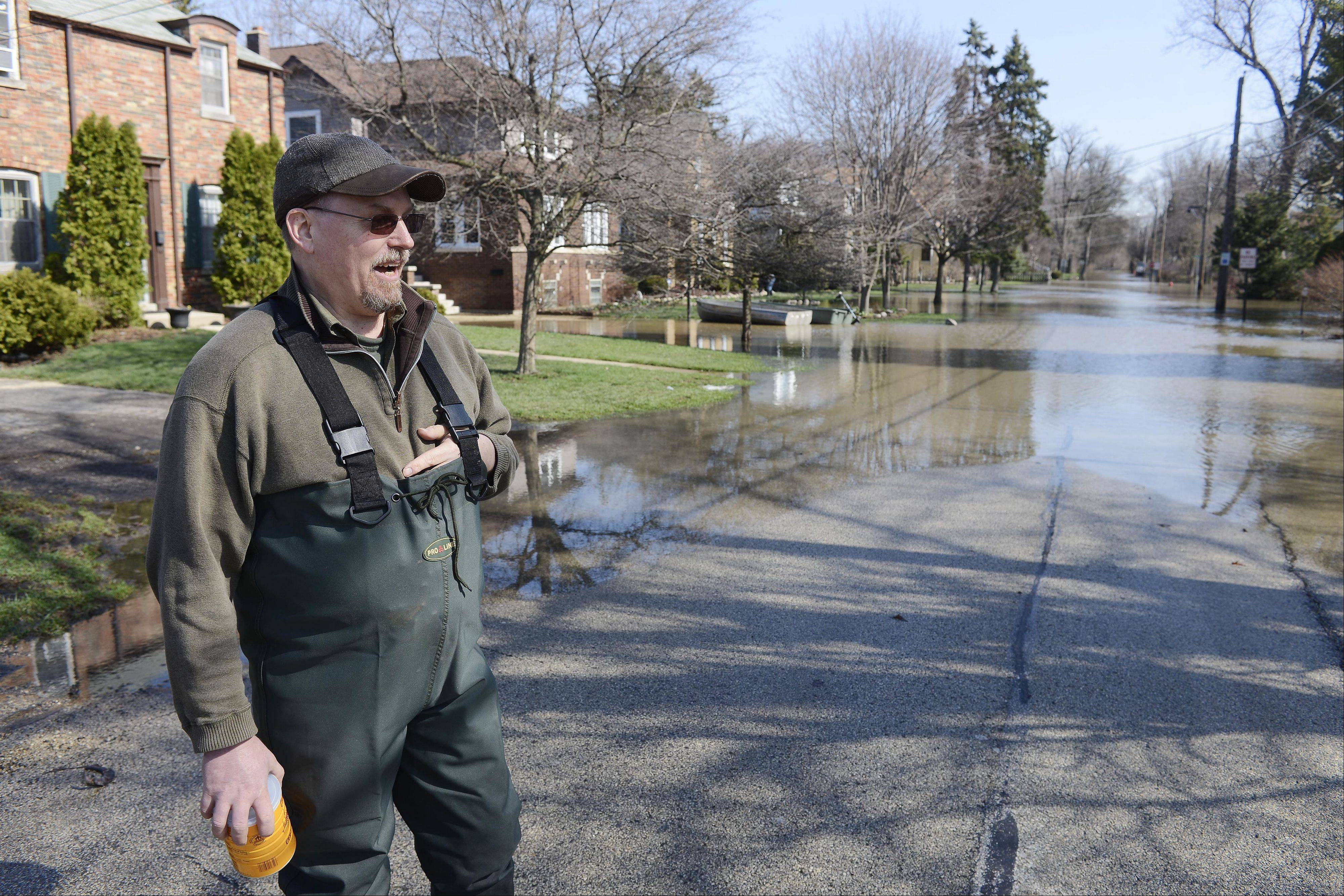 "Kerry Chambers talks about Des Plaines River flooding in the Big Bend area while standing along Hawthorne Lane in Des Plaines Monday. ""The water has to go down another couple of feet before I can pump,"" he said of his home on Hawthorne Terrace."