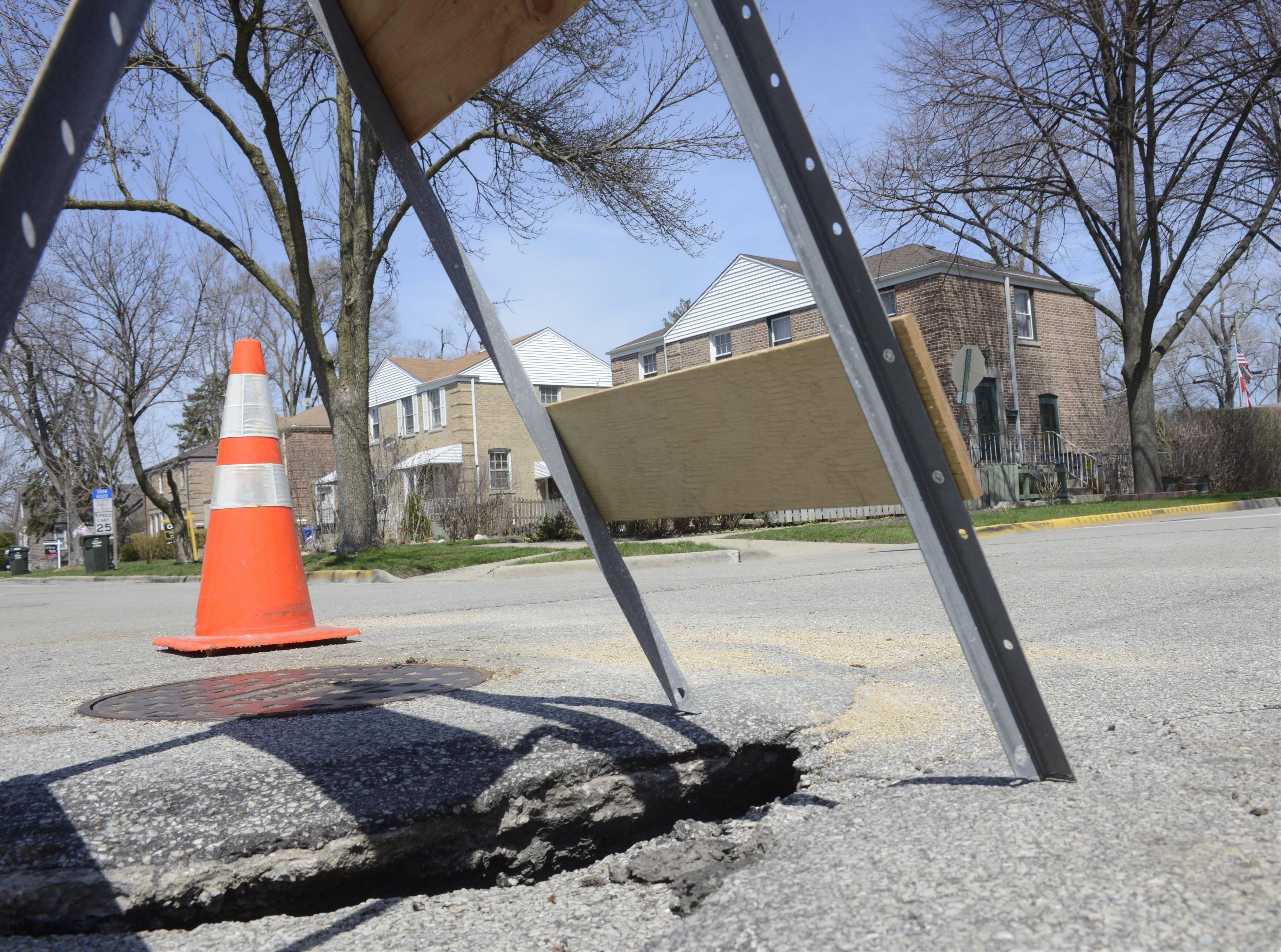 The pavement around a manhole cover is sinking at the intersection of Riverview Avenue and White Street in Des Plaines.