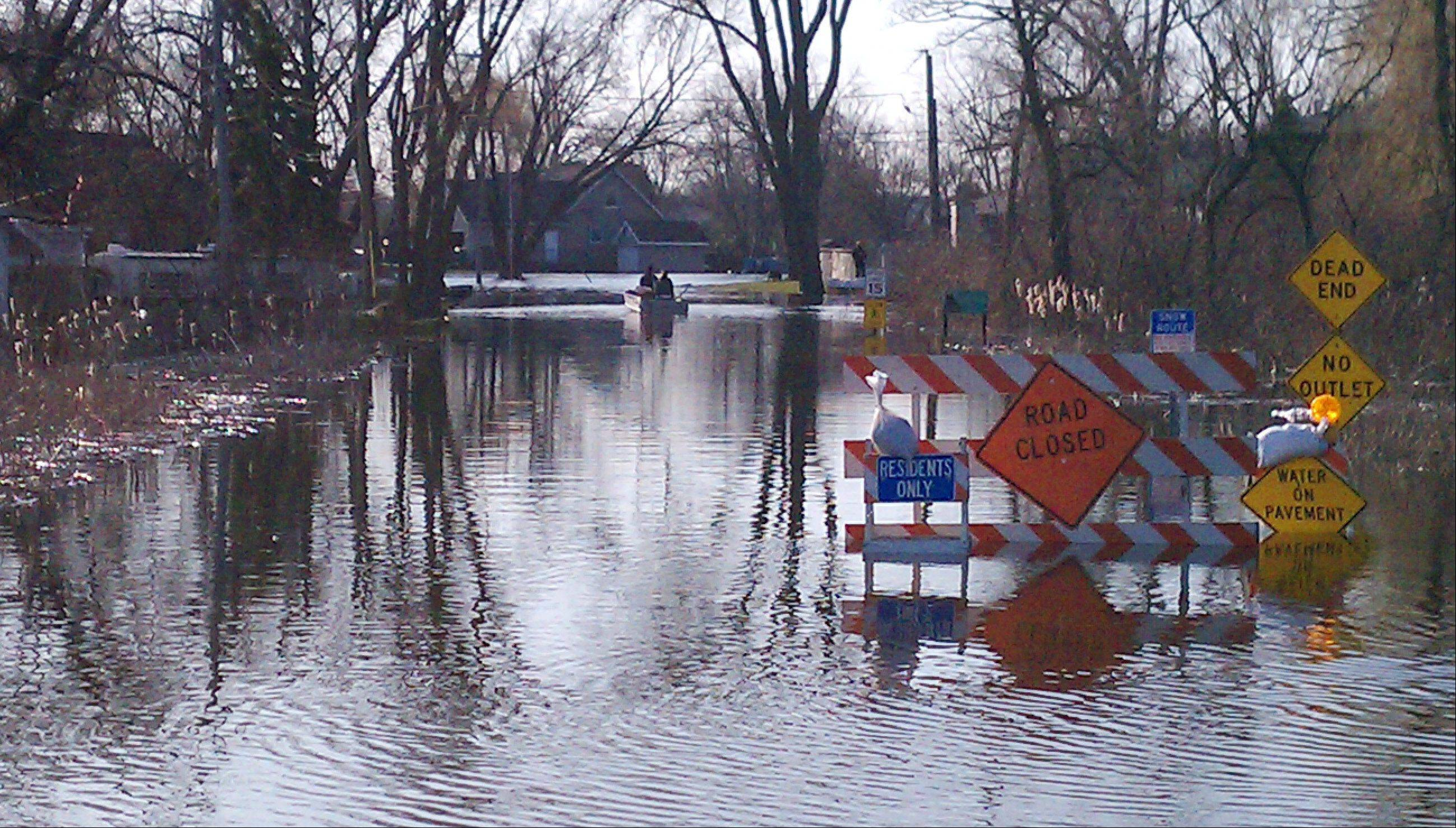 Homeowners use a boat on Knollwood Drive in Fox Lake Monday.