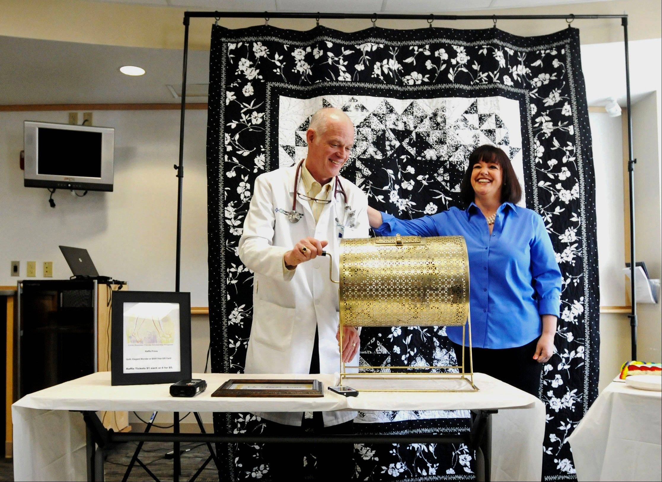Dr. Terence Glennon, left, a physiatrist at the Rehabilitation Institute of Chicago at Herrin Hospital and Carla Shasteen, of Herrin pull a name out of a basket during a quilt giveaway in Herrin.
