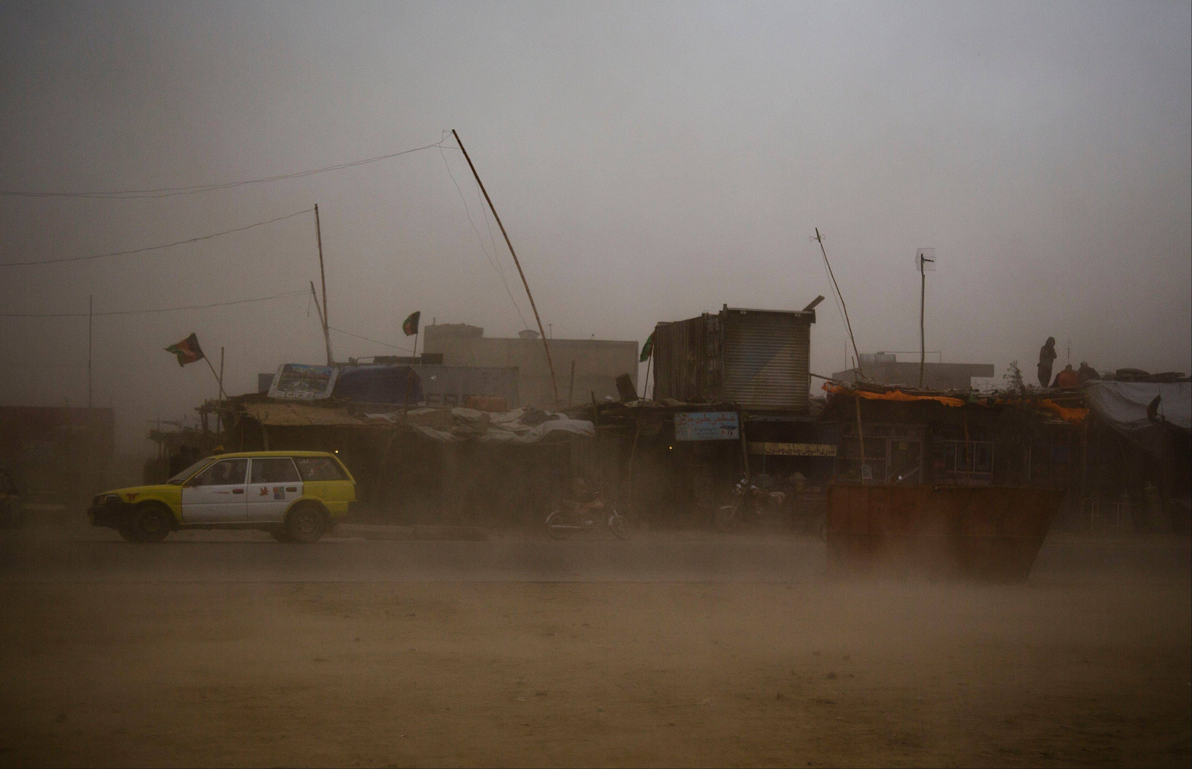 A taxi tries to make its way through a sandstorm that obscures the city of Kanadahar, Afghanistan, Sunday. A Turkish transport helicopter carrying at least 11 civilians was forced to make an emergency landing in a Taliban-controlled area in eastern Afghanistan, and the insurgents took all the people on board prisoner, including eight Turks and a Russian, officials said Monday.
