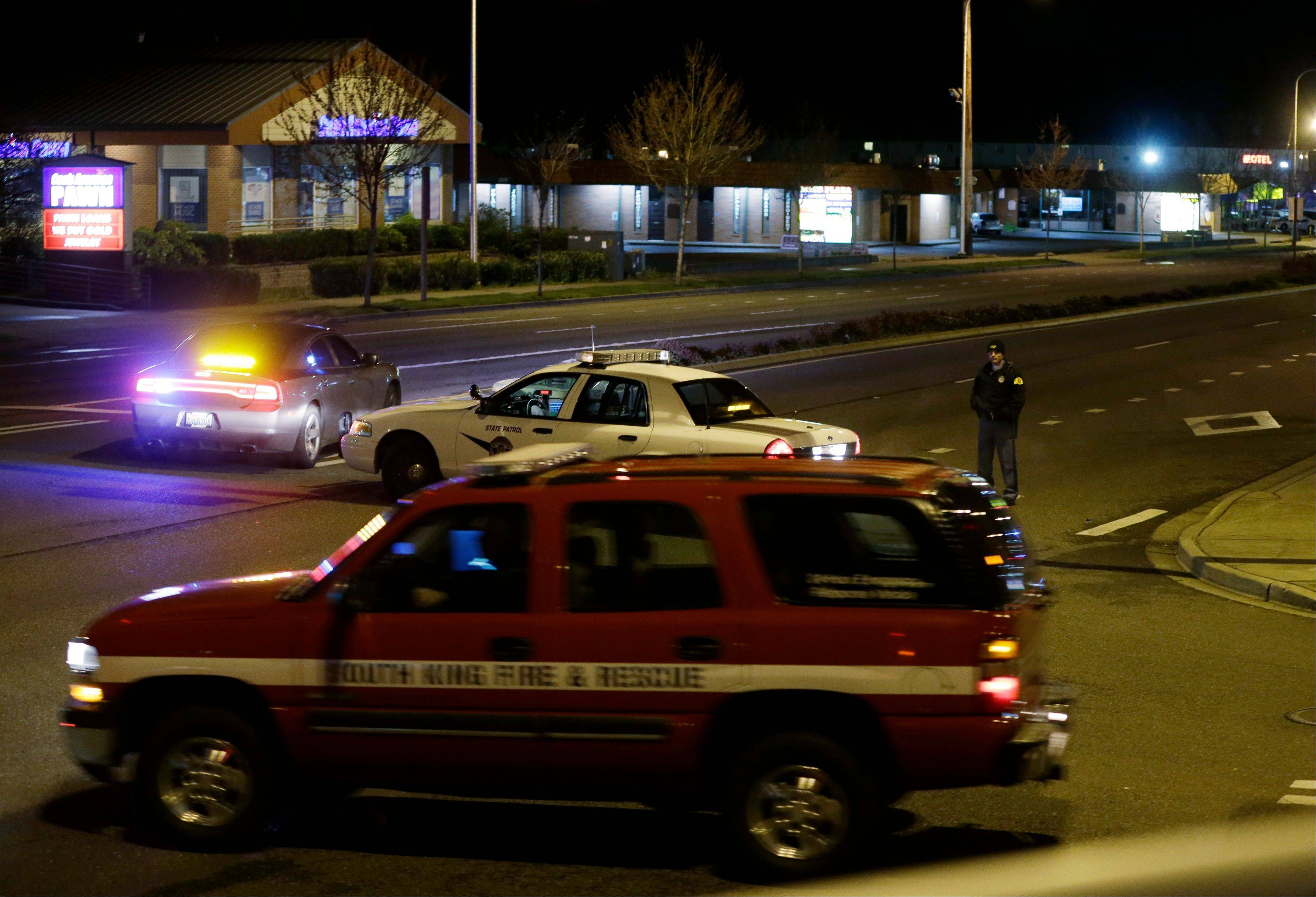 Police and fire vehicles are seen several blocks from the scene of an overnight shooting that police said left five people dead Monday at an apartment complex in Federal Way, Wash.